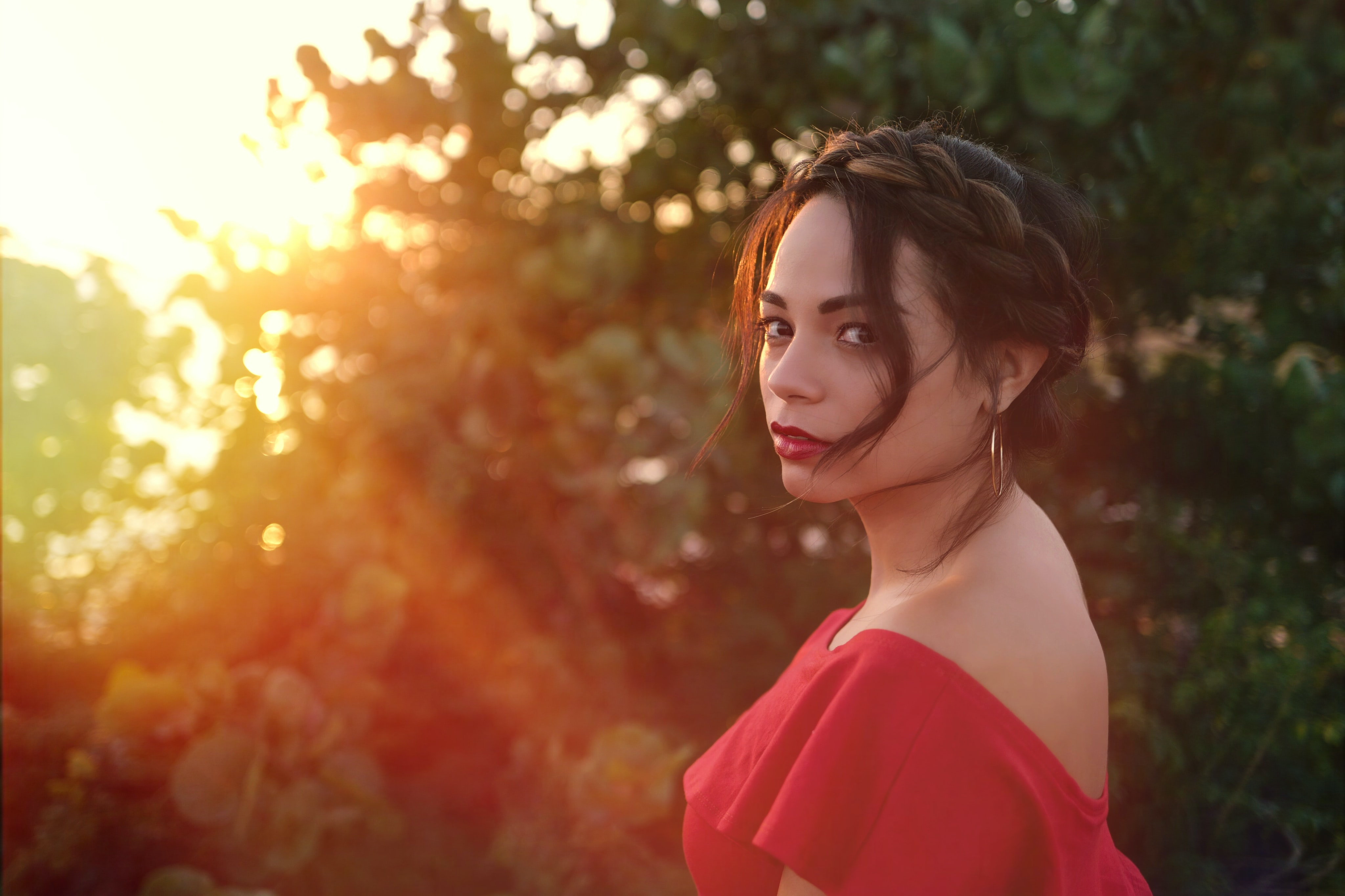 Woman in a red dress looks over her shoulder at sunset
