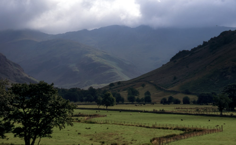 cloudy sky over mountains and grass field