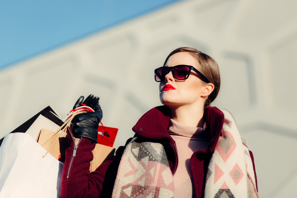 High fashion woman wearing sunglasses with a handful of shopping bags