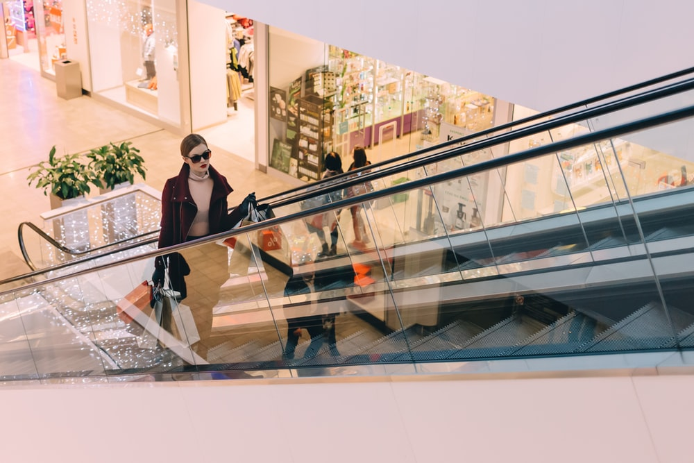Chic woman in sunglasses holds bags up a mall escalator