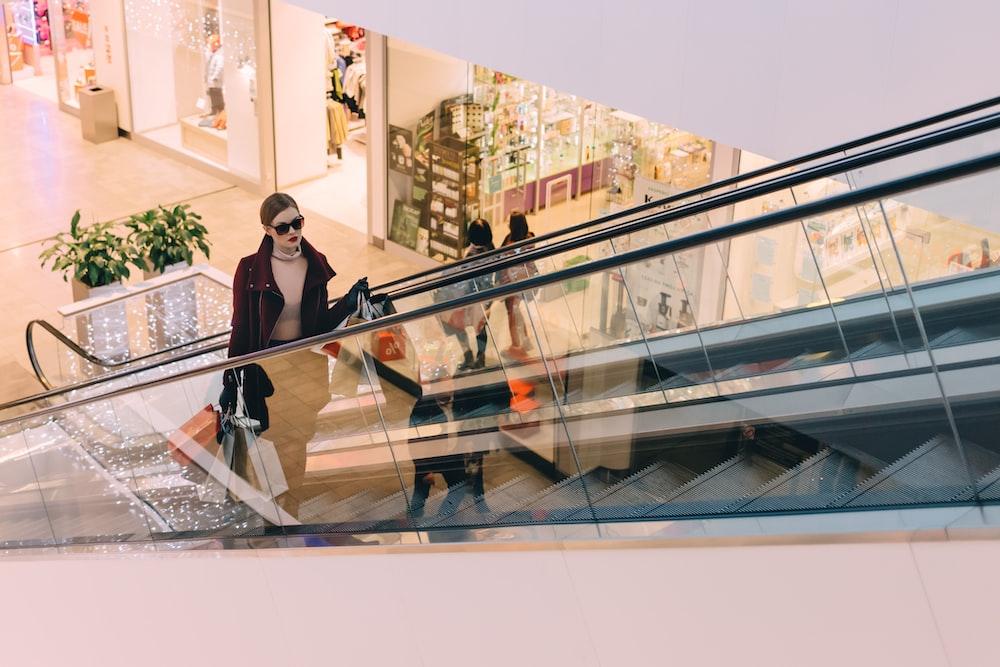 woman riding escalator