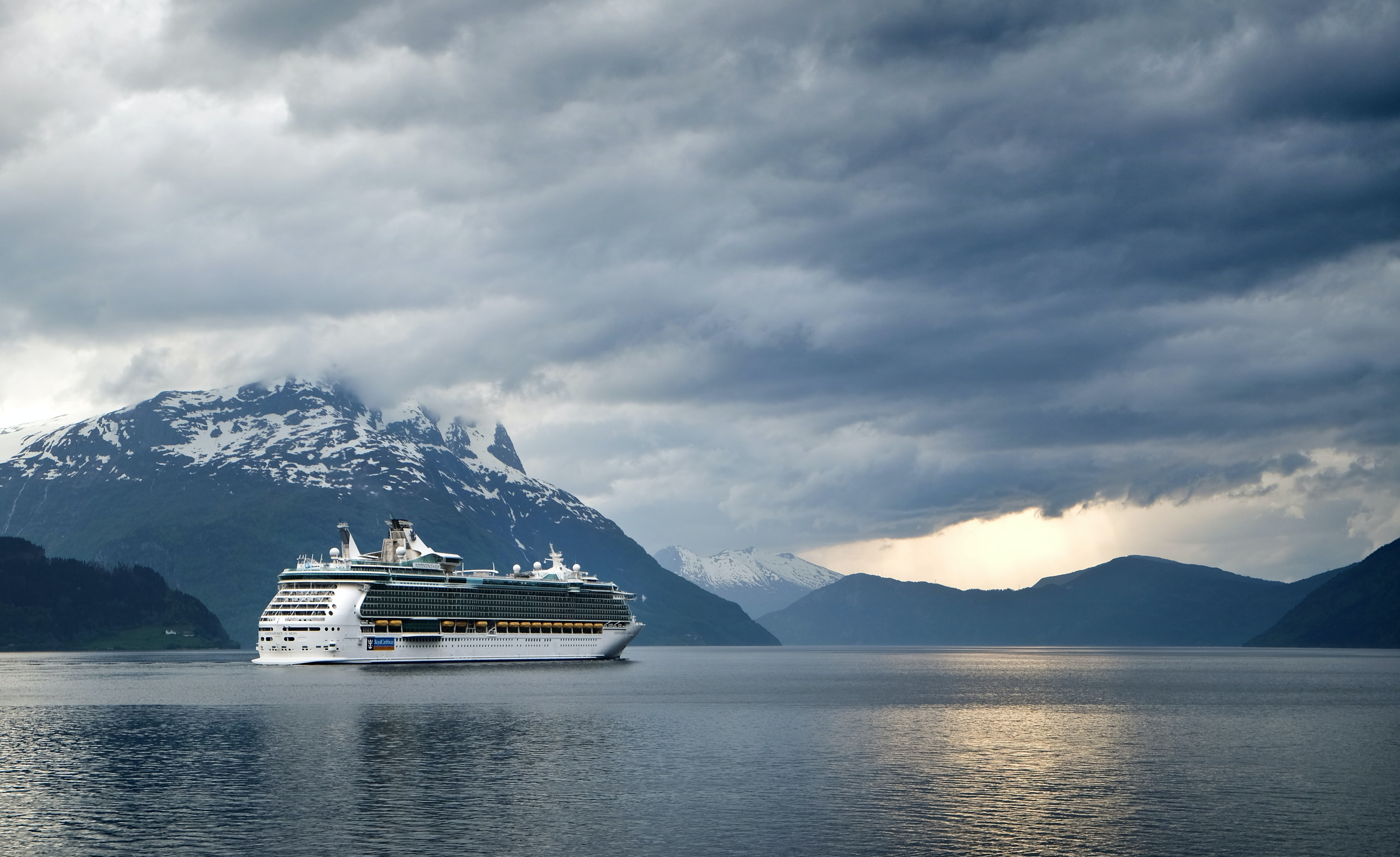 A cruise ship on a mountain lake with heavy clouds above