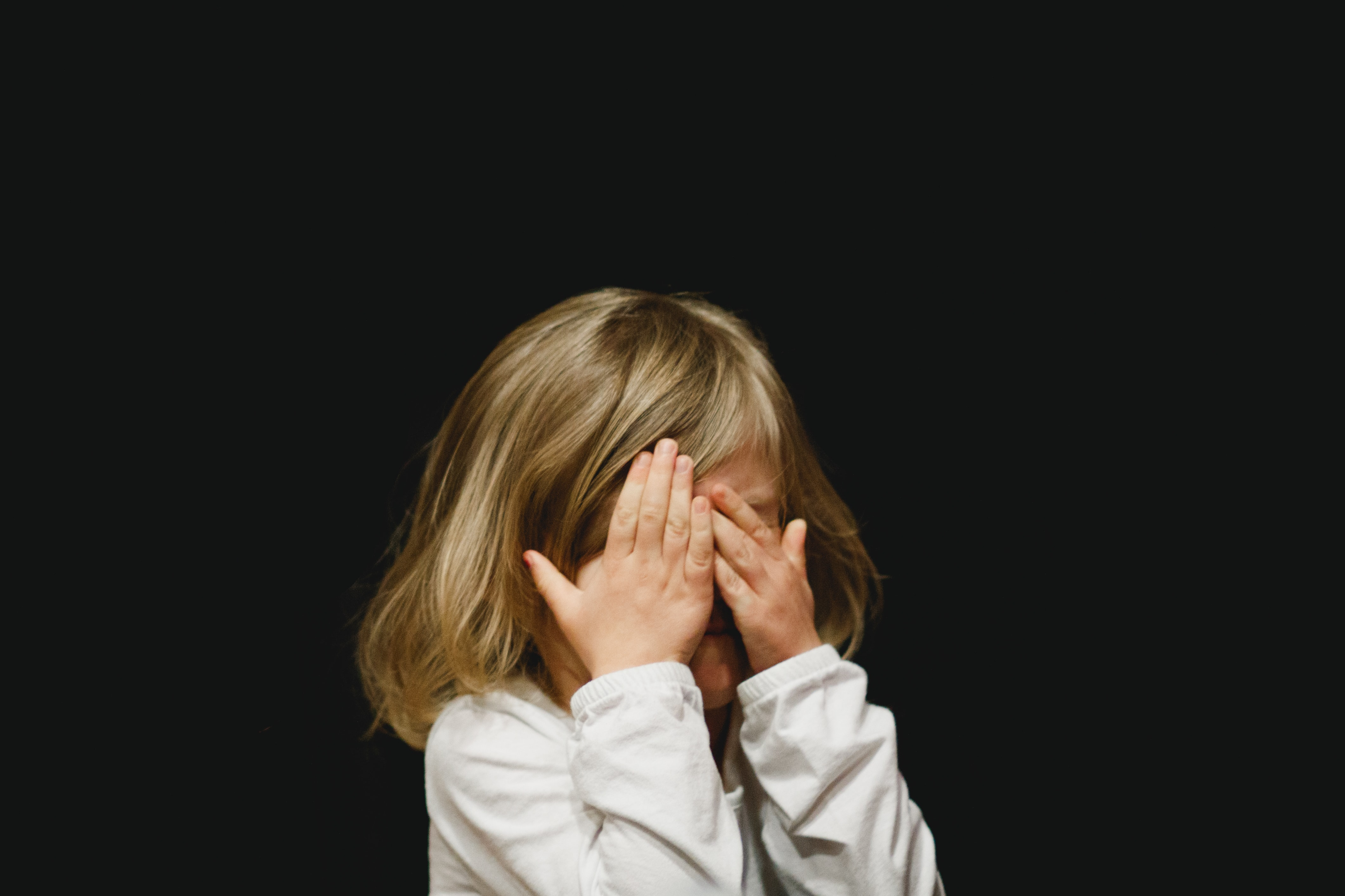 Little blonde hair girl covering her face with hands