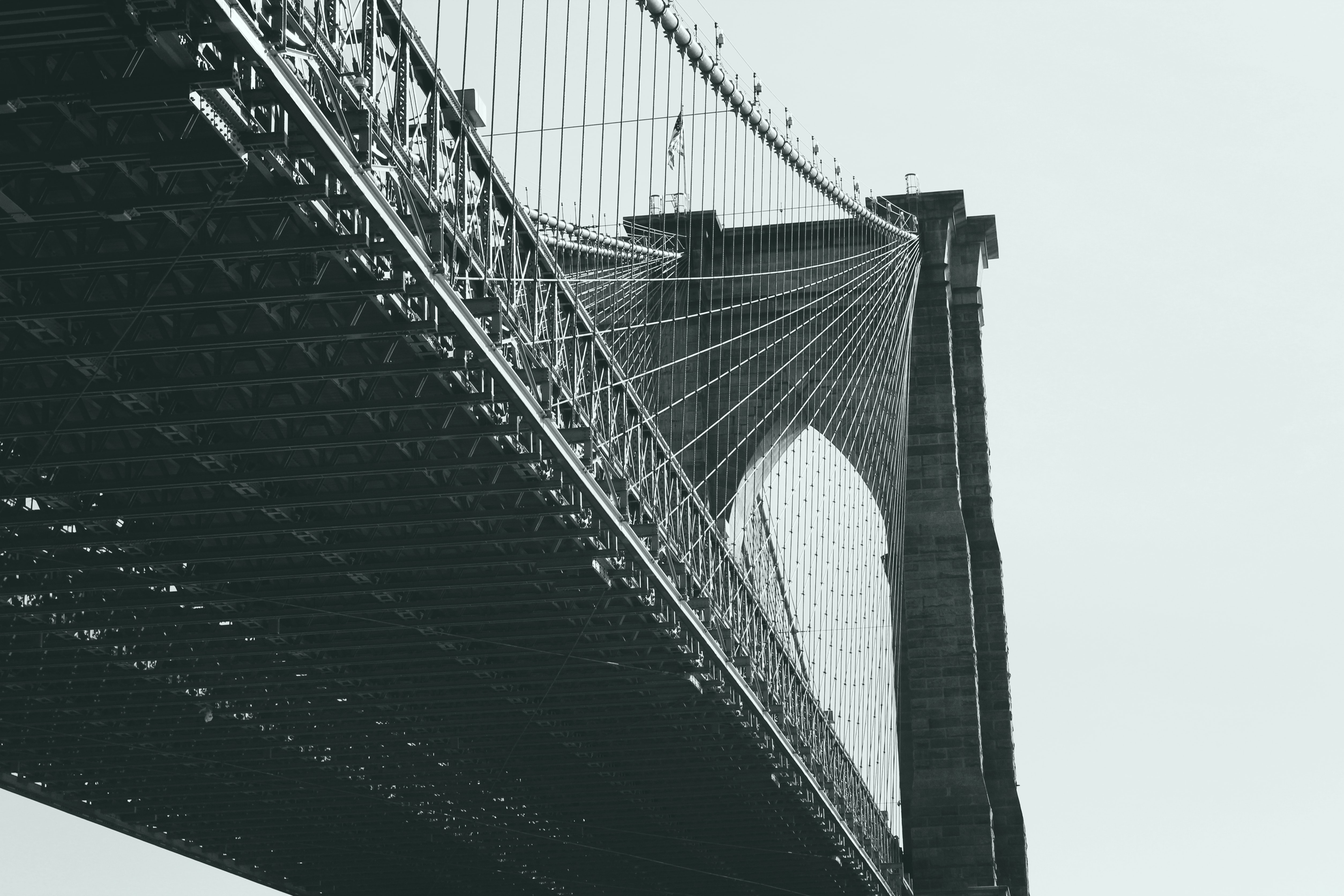 Black and white shot of Brooklyn Bridge from below with clear sky