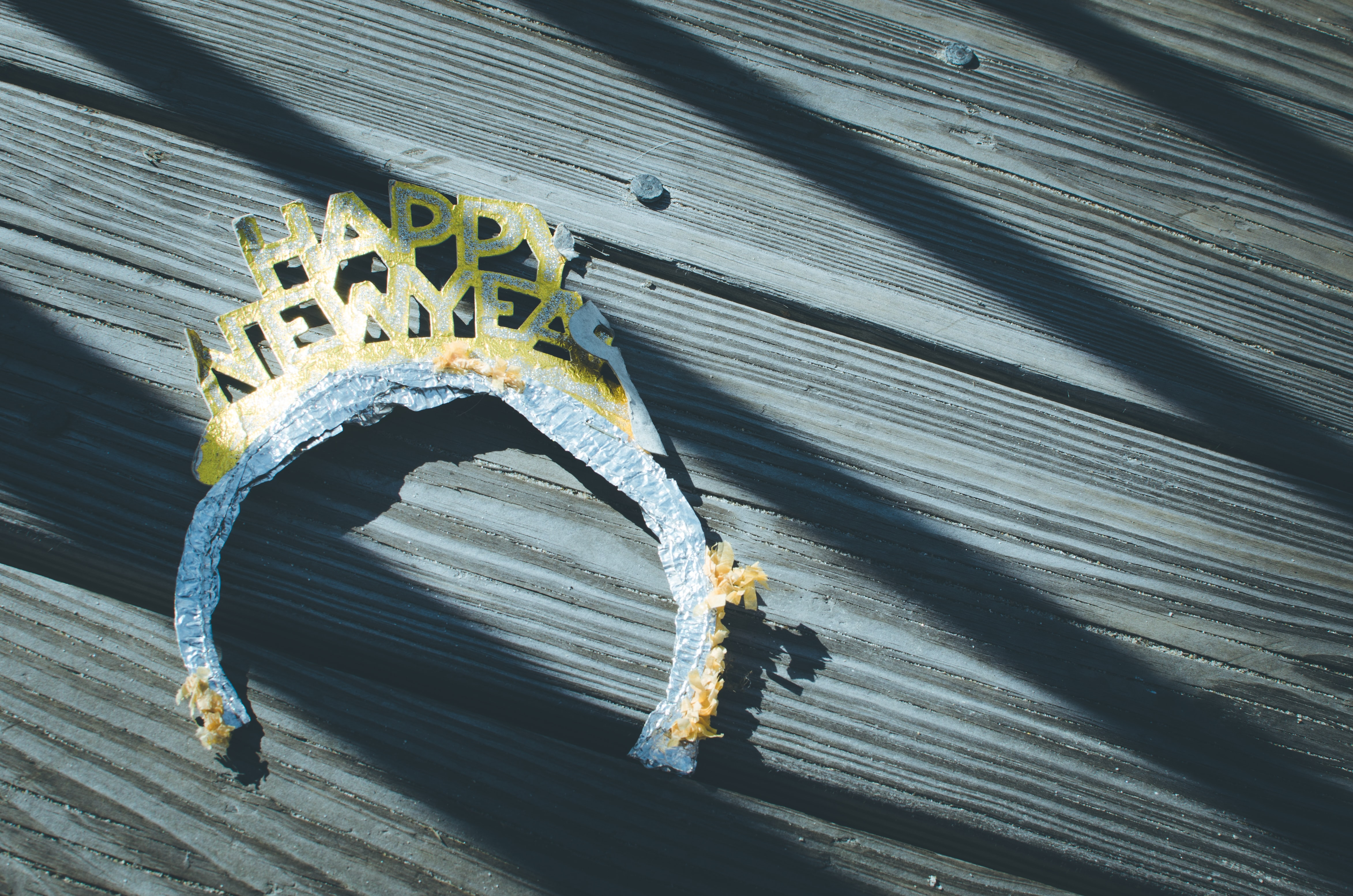 A discarded old Happy New Year headband on wooden floorboards, Ocean City