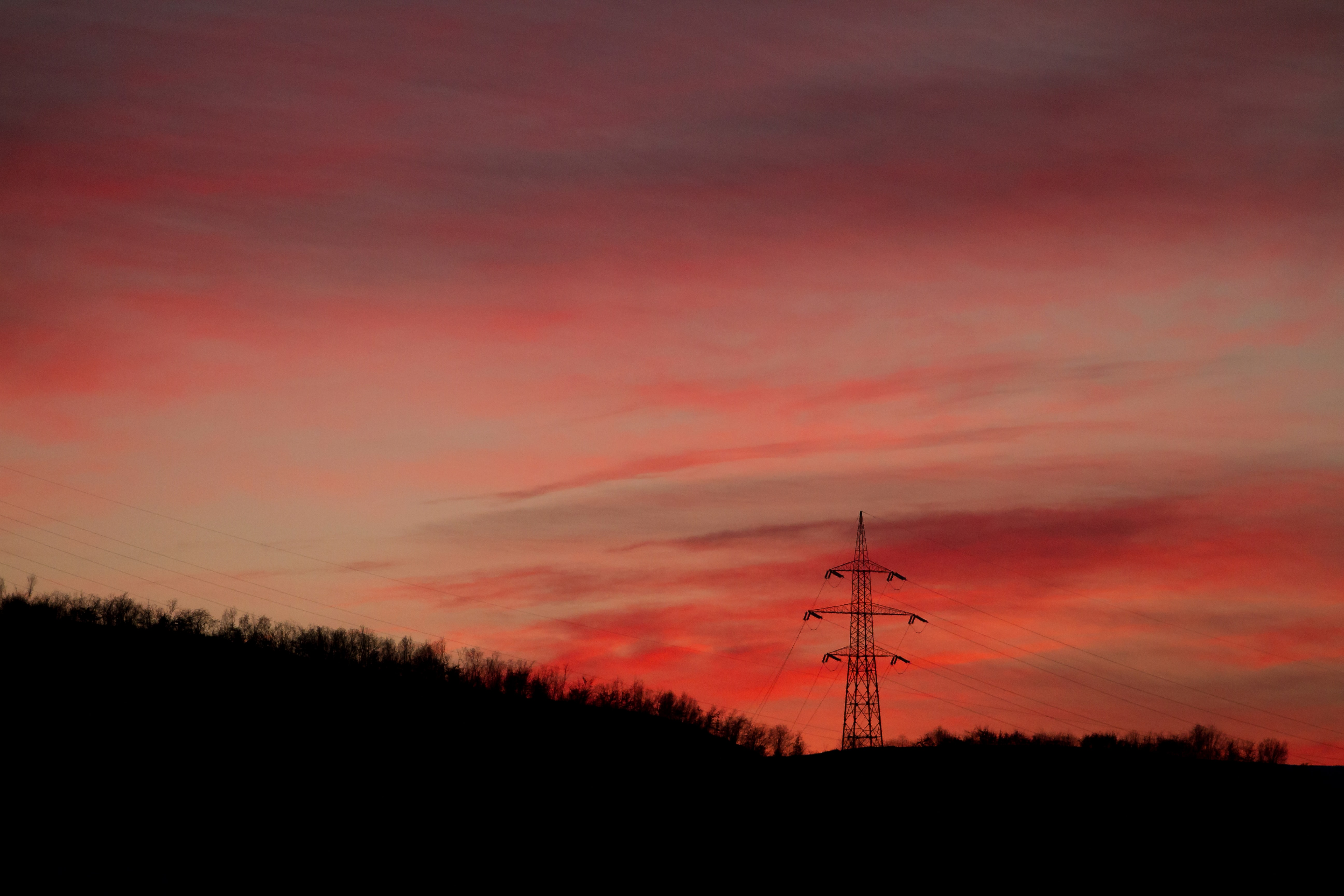 A transmission tower among trees under a red sky at dusk