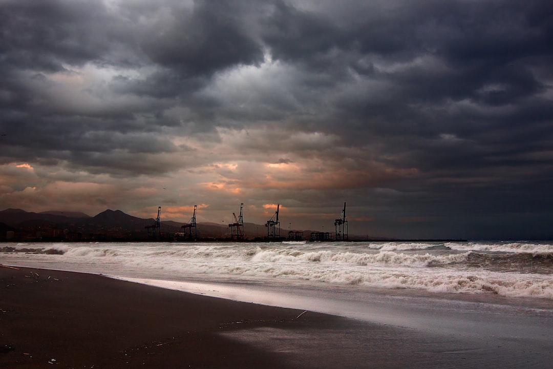 Había temporal de levante cuando fui a ver y fotografiar este amanecer desde la Playa de la Misericordia con el Puerto de Málaga y sus grúas al fondo.