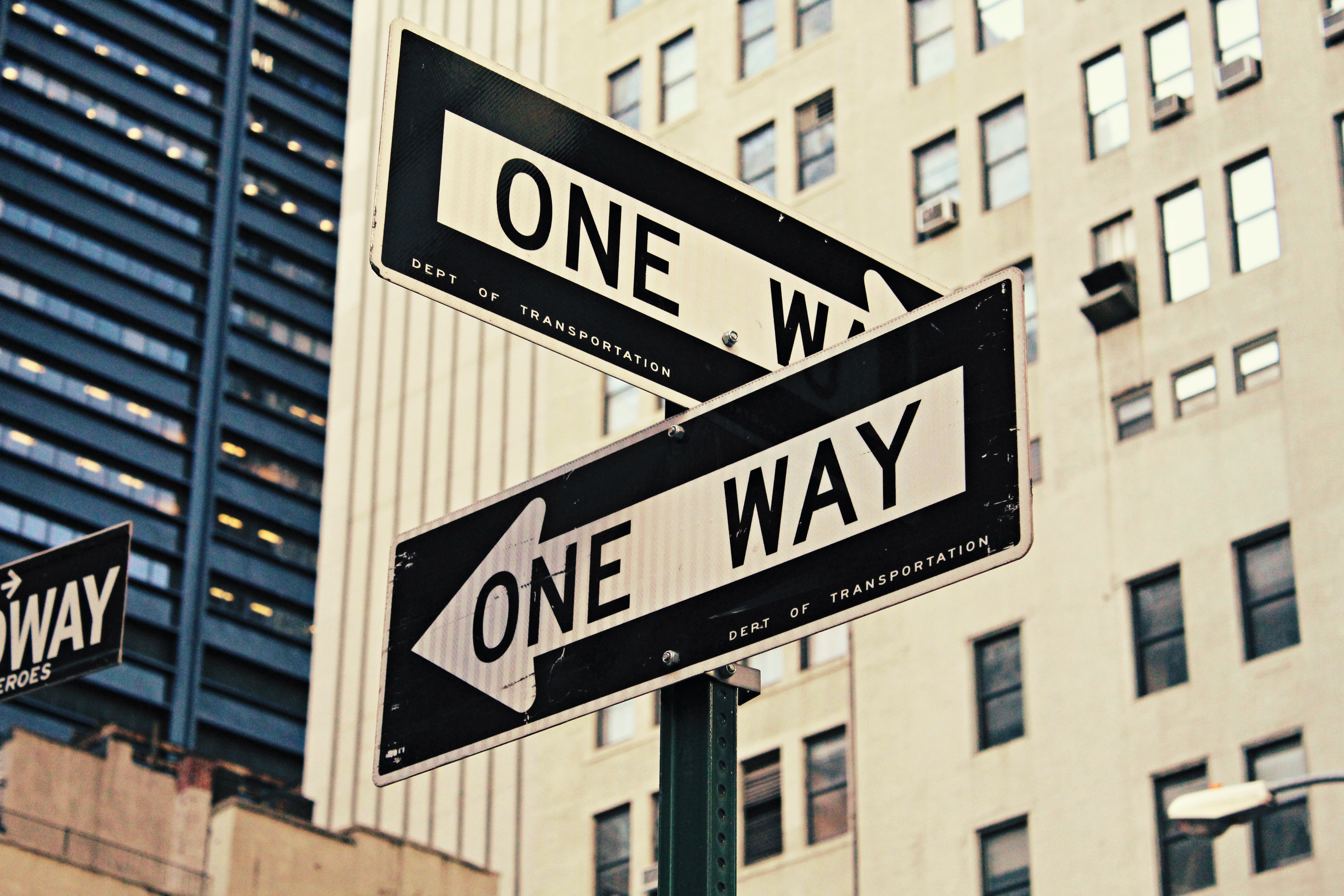 "Two ""one-way"" signs with arrows going different ways on a street in New York"