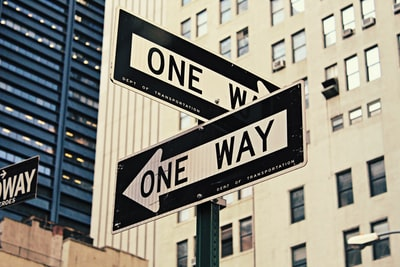 white and black one way-printed road signages sign teams background