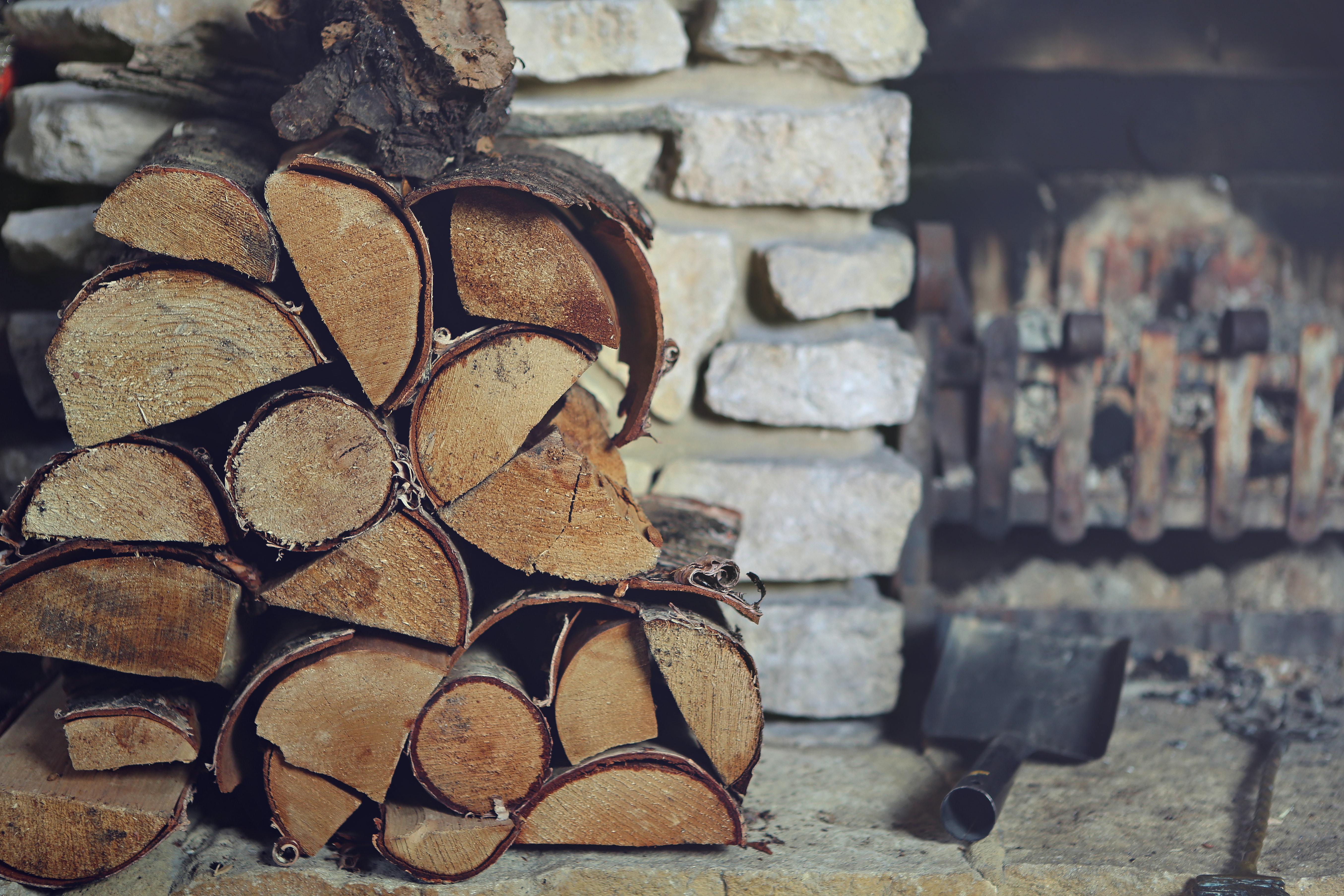 A stack of firewood next to a small fireplace