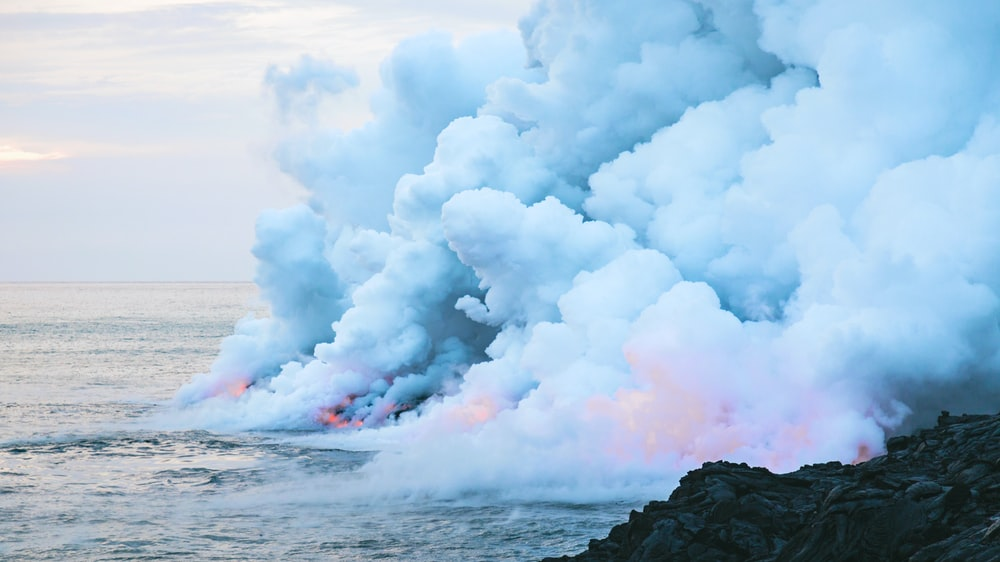 fire and smoke on body of water near rock formation under cloudy sky