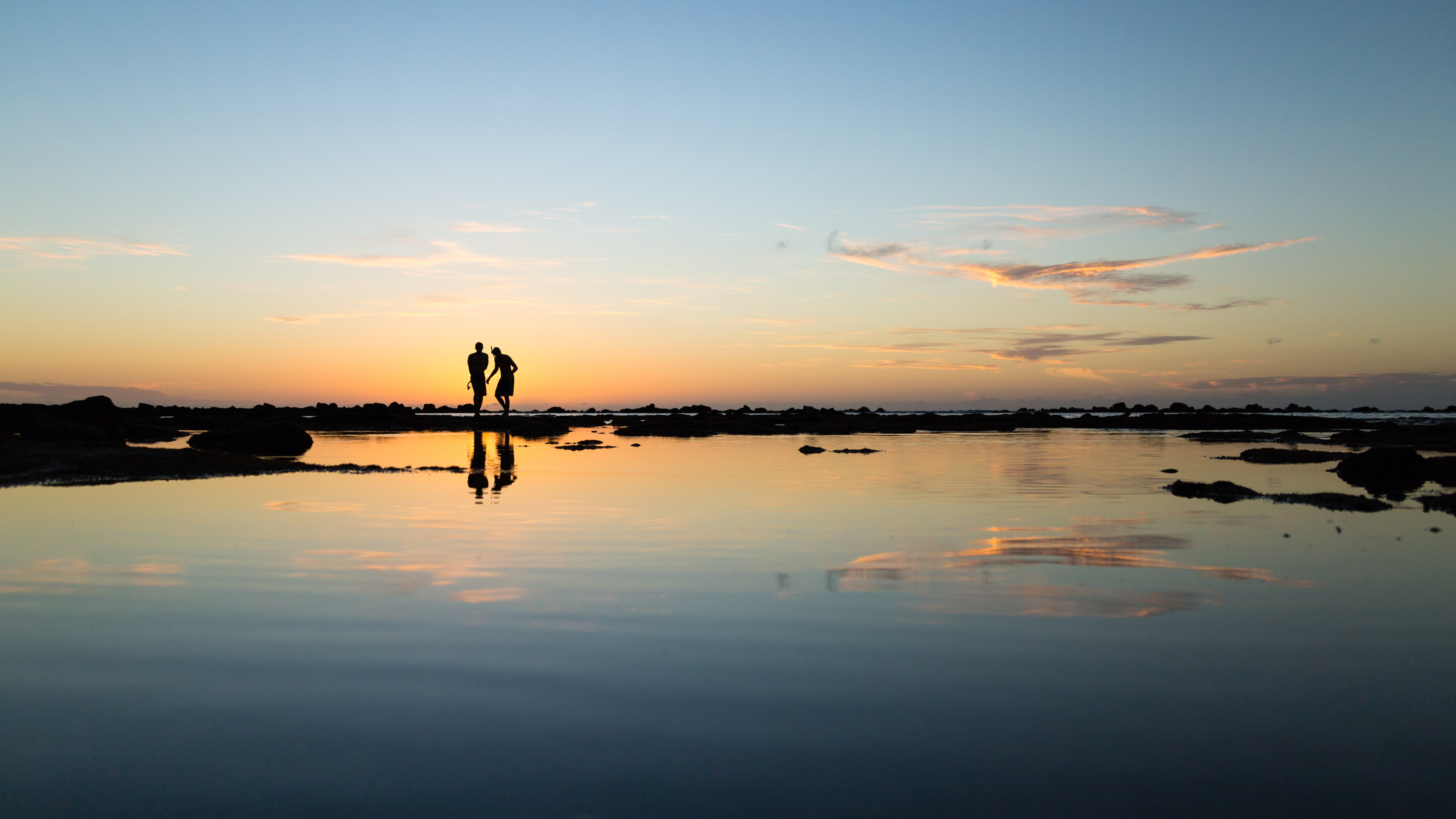 A silhouetted couple stand together on the horizon as they and the blue and yellow sky reflect into the still water foreground