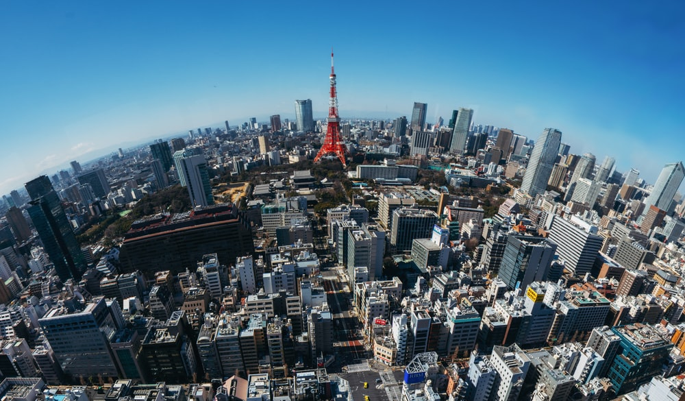 fish eye photography of red and white tower and cityscape