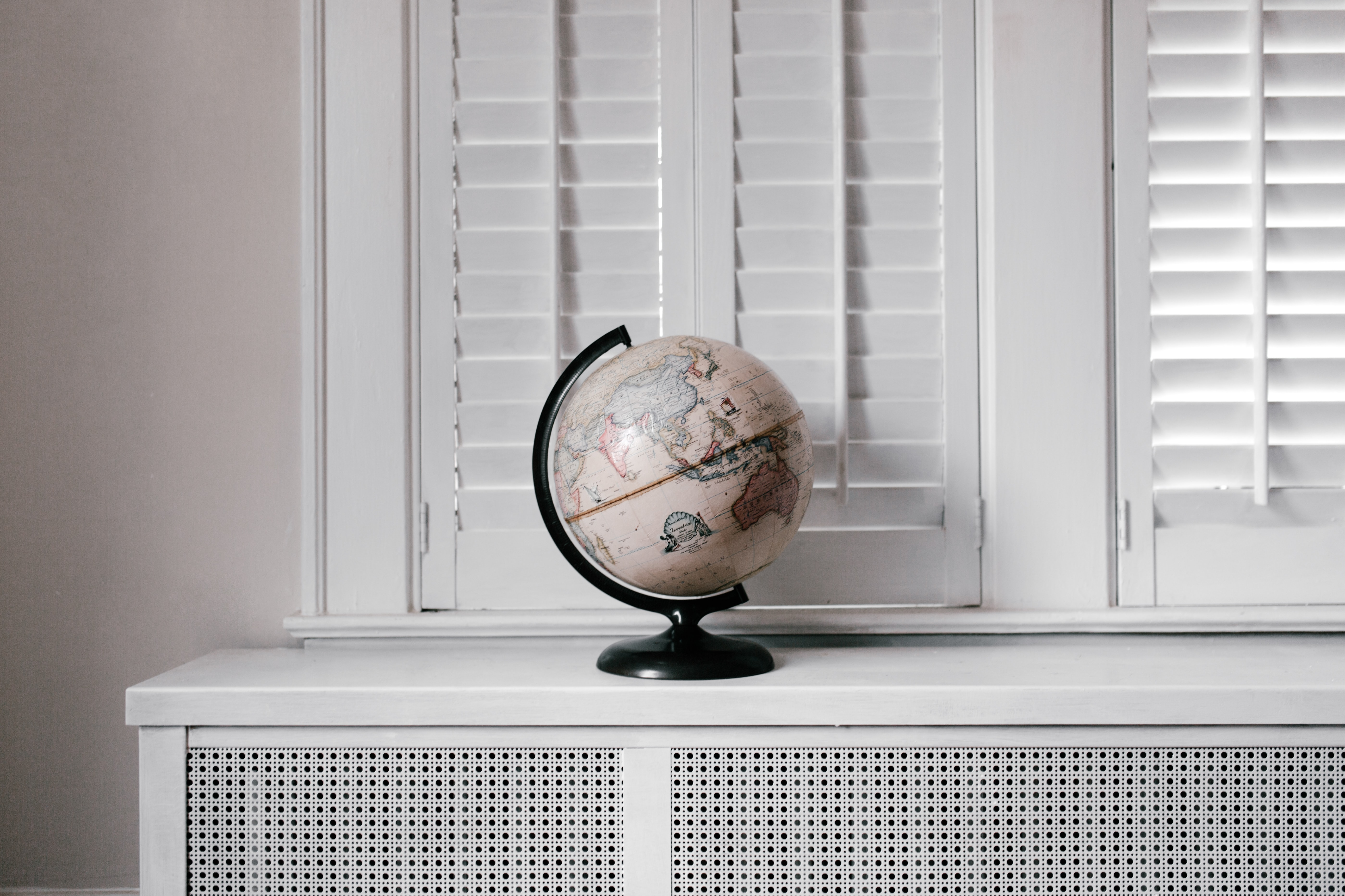 A cream colored globe of the Earth sits in a in a completely white room