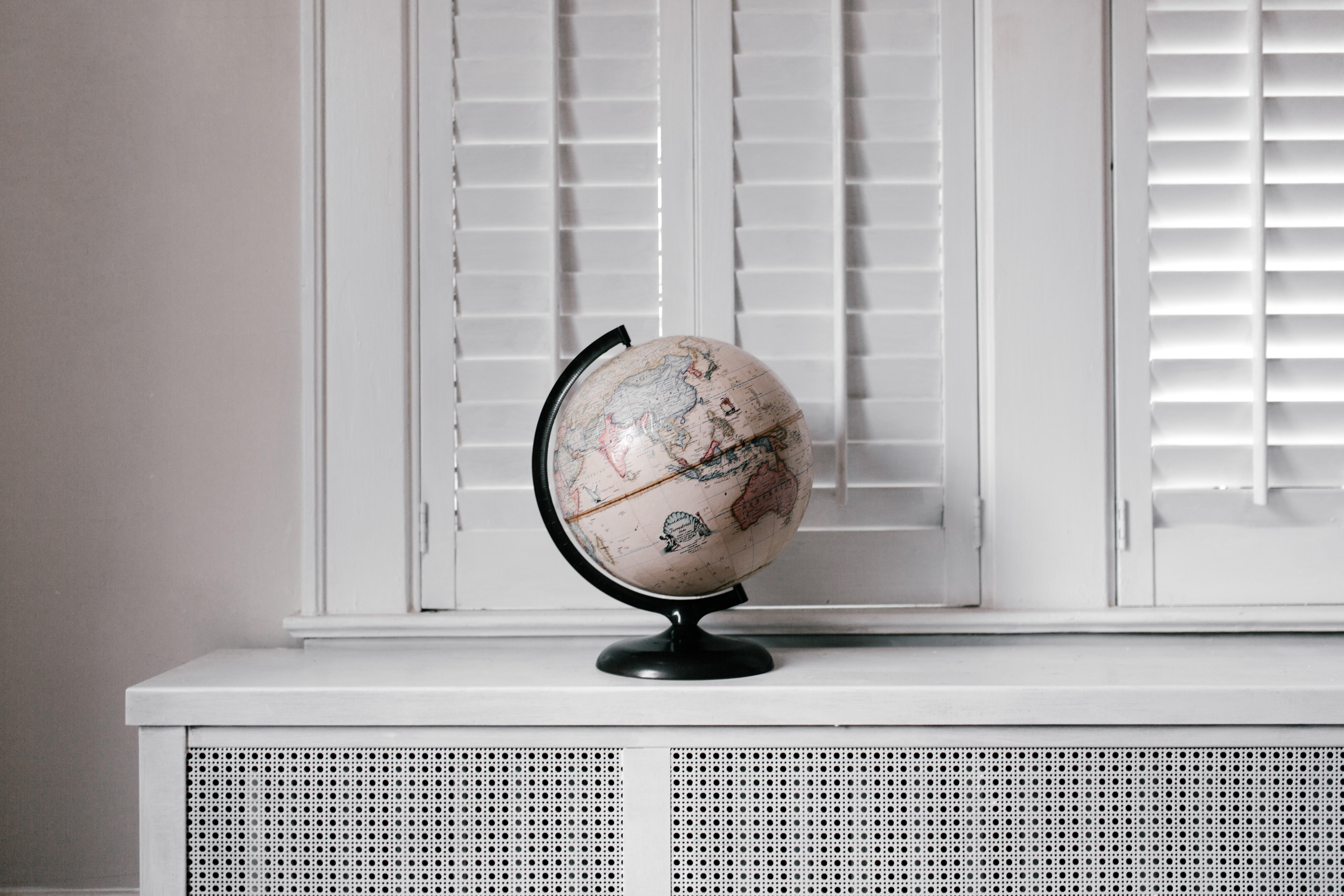 beige desk globe on white desk