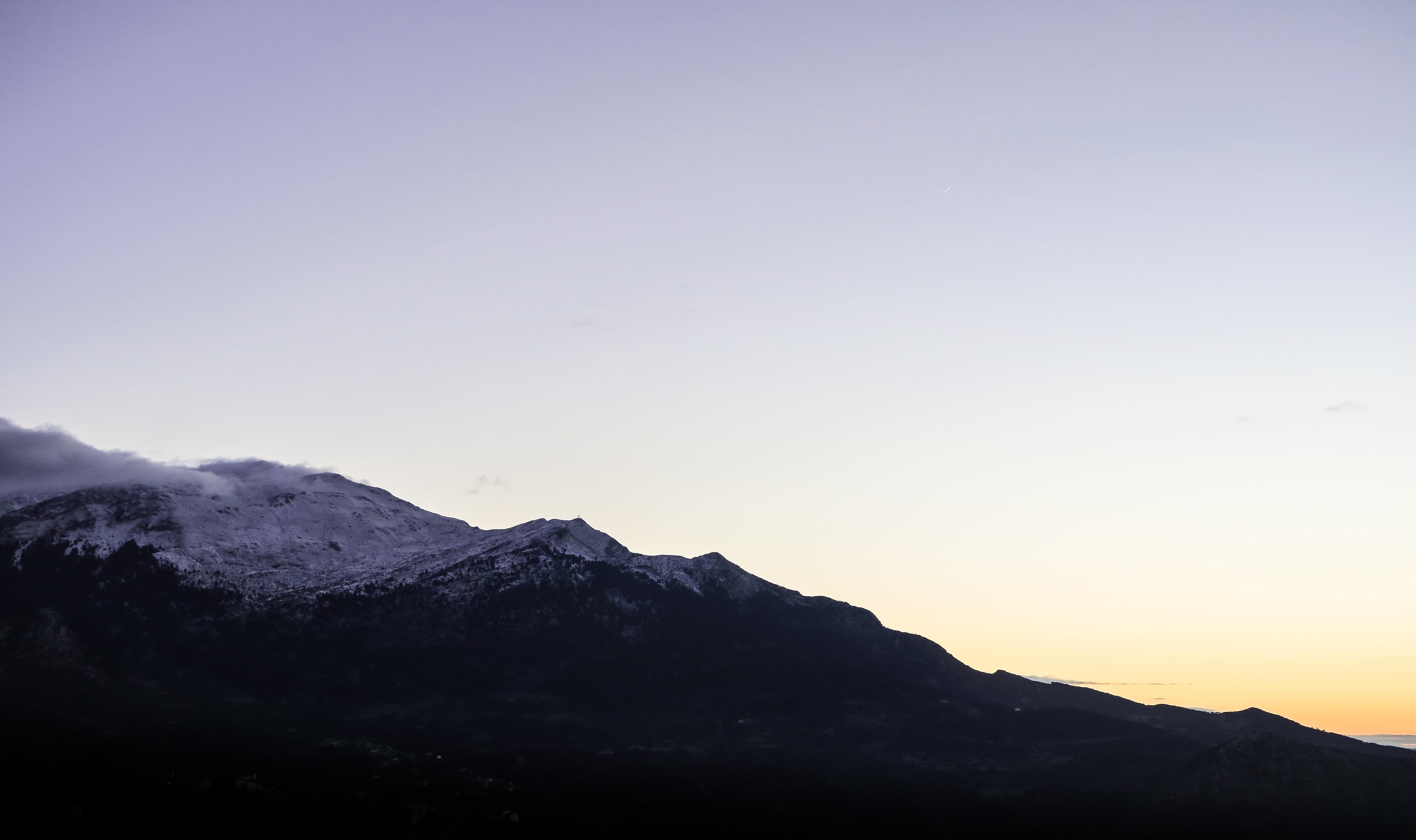 A dim shot of a long mountain ridge during sunset