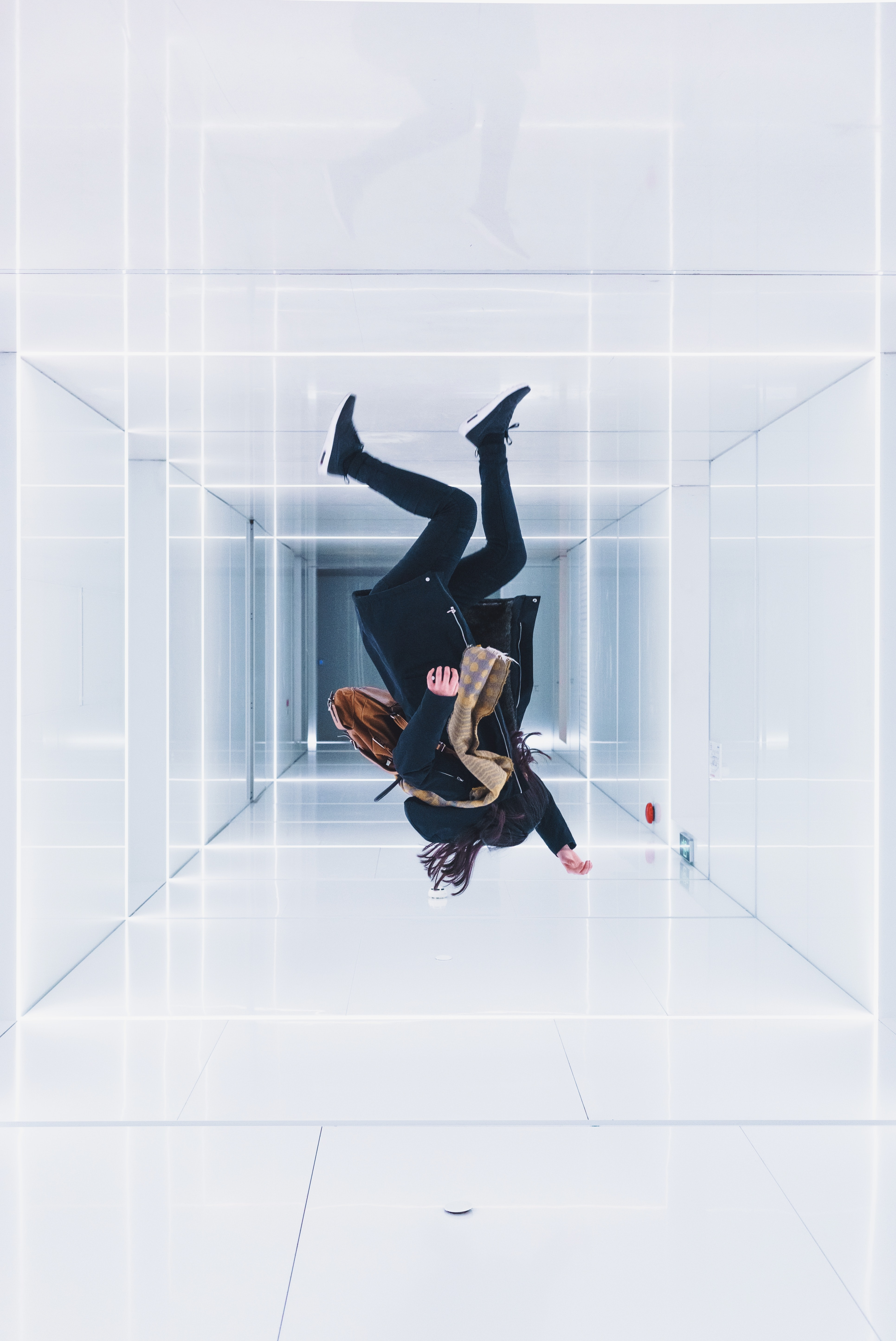 Optical illusion of a person jumping upside down in a white walled room