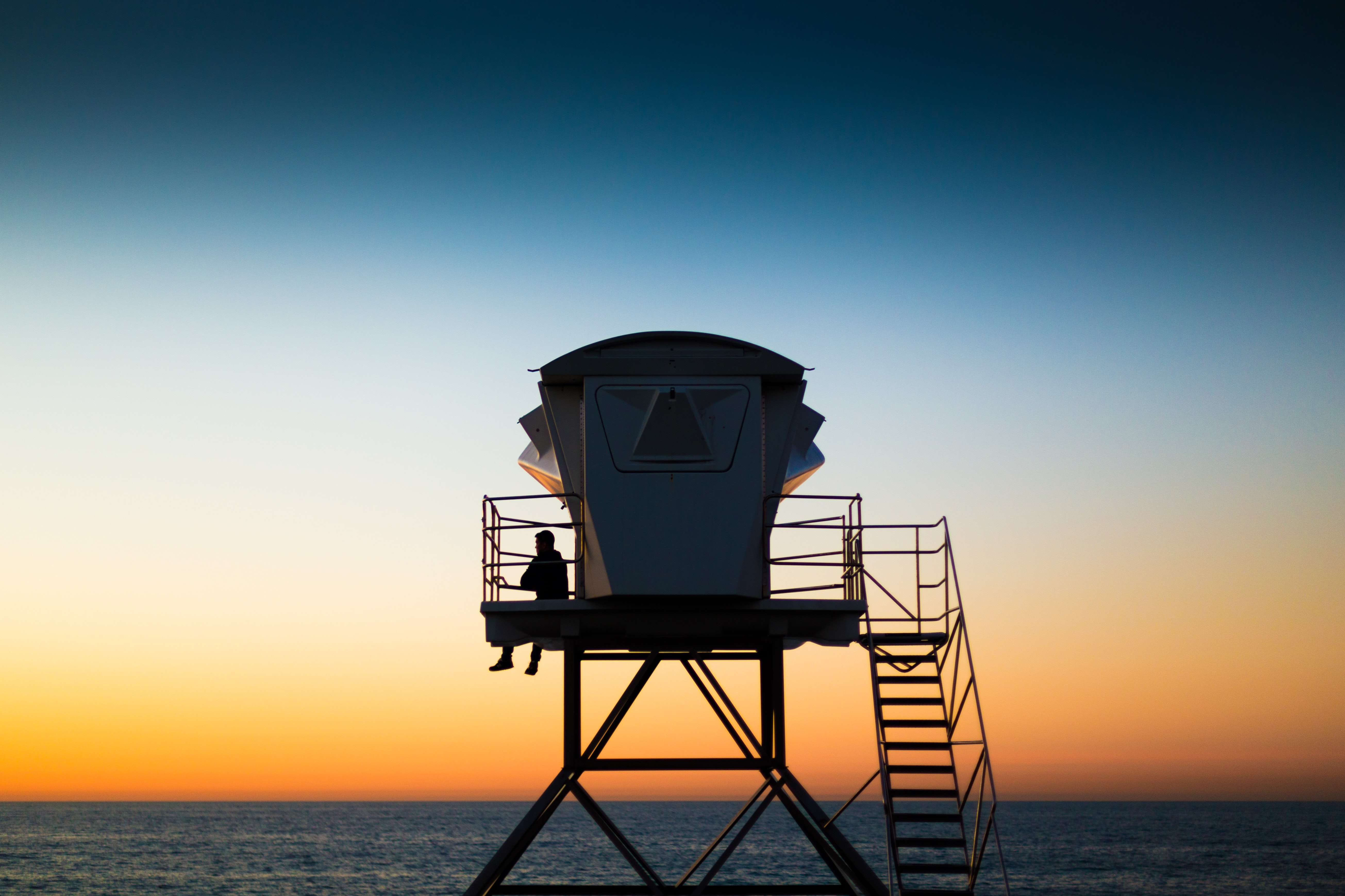 Silhouette of a man sitting alone against railing of a lifeguard tower, ocean and dusky sky in the background