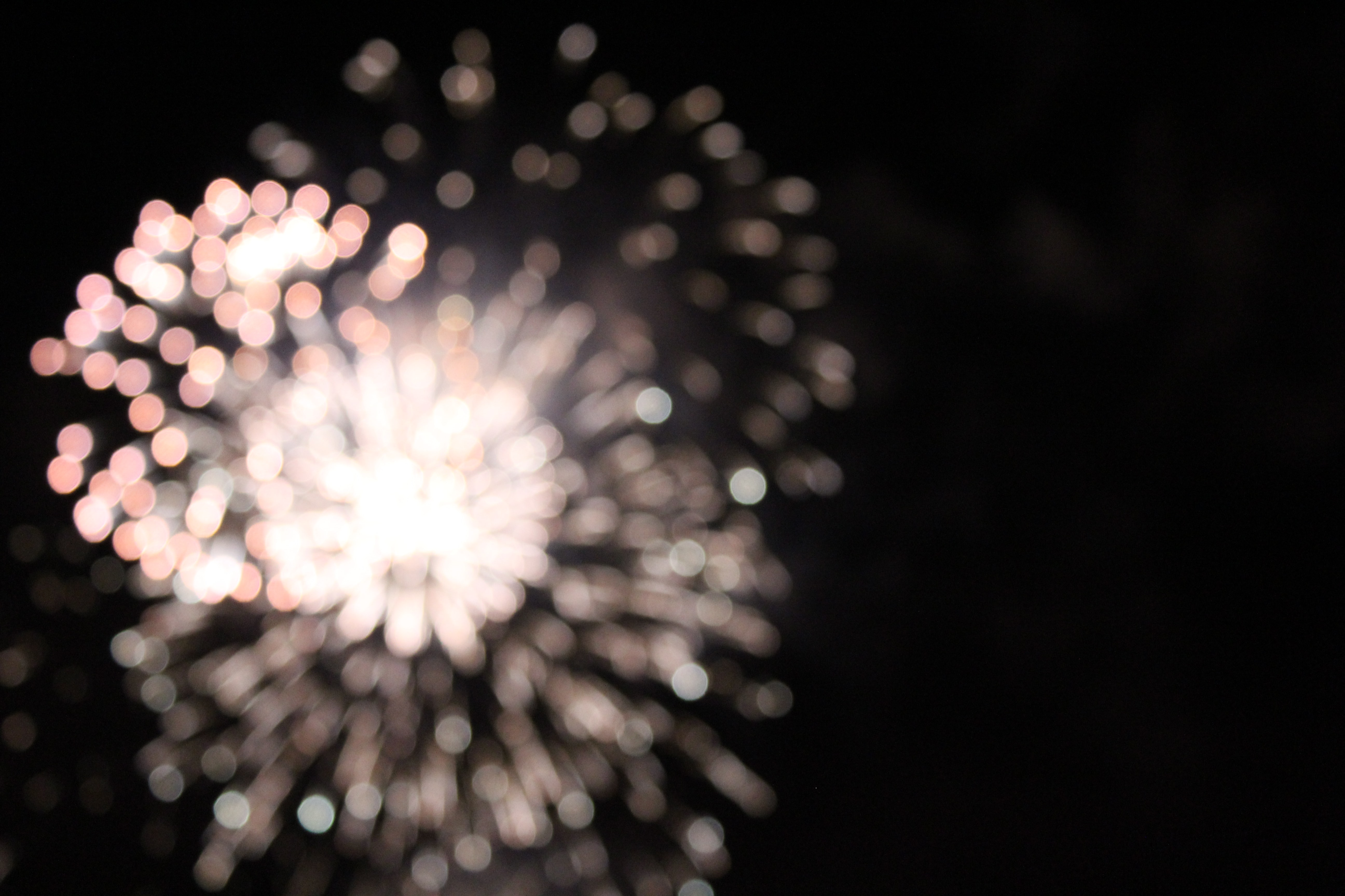 Out of focus firework in mid-explosion at night