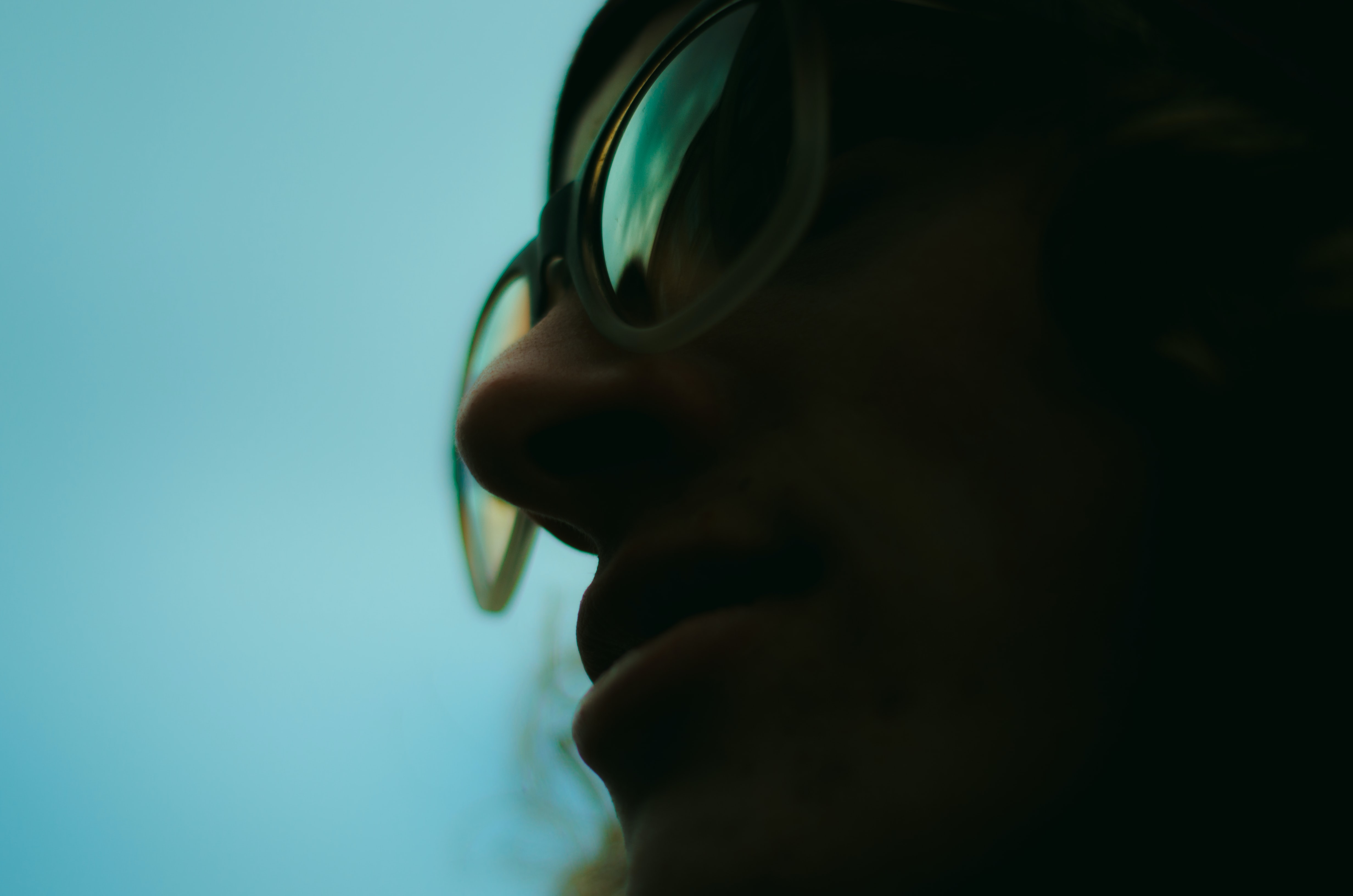 close up photo of person wearing glasses with teal background