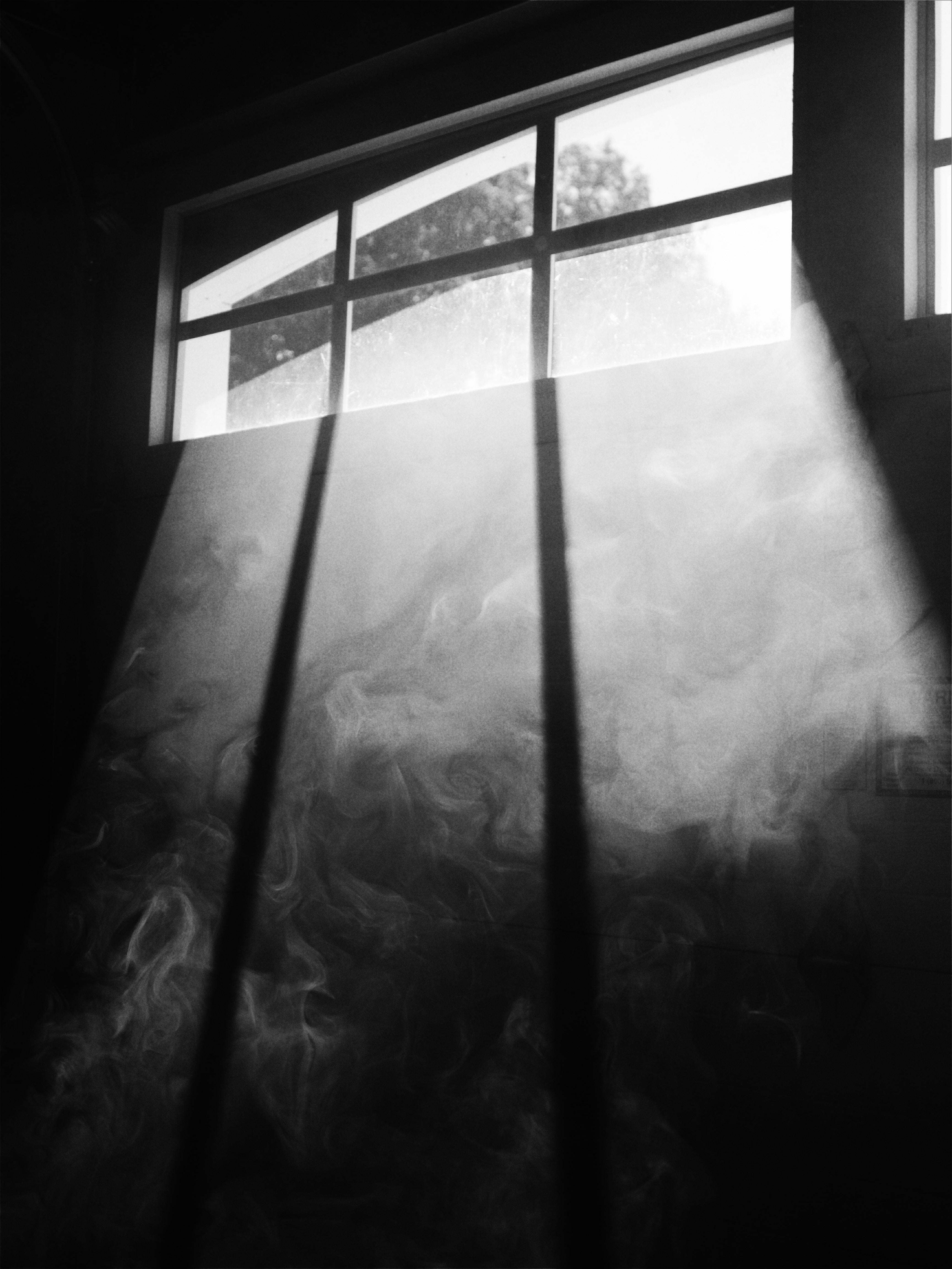 Smoke rising near a sunlit window from a garage