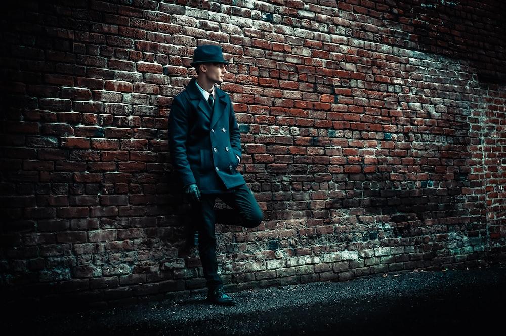 man wearing black coat leaning on brown brick wall