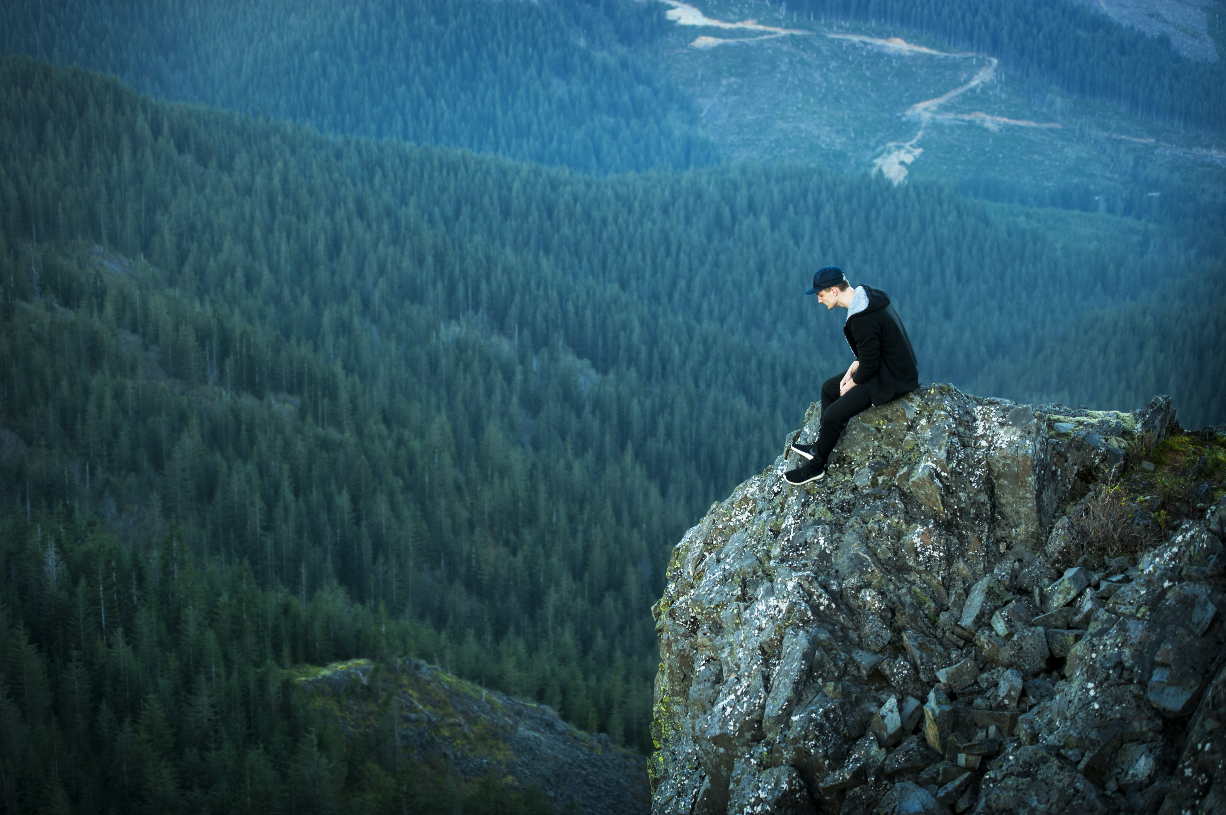 A man in a cap sitting on a ledge overlooking wooded hills