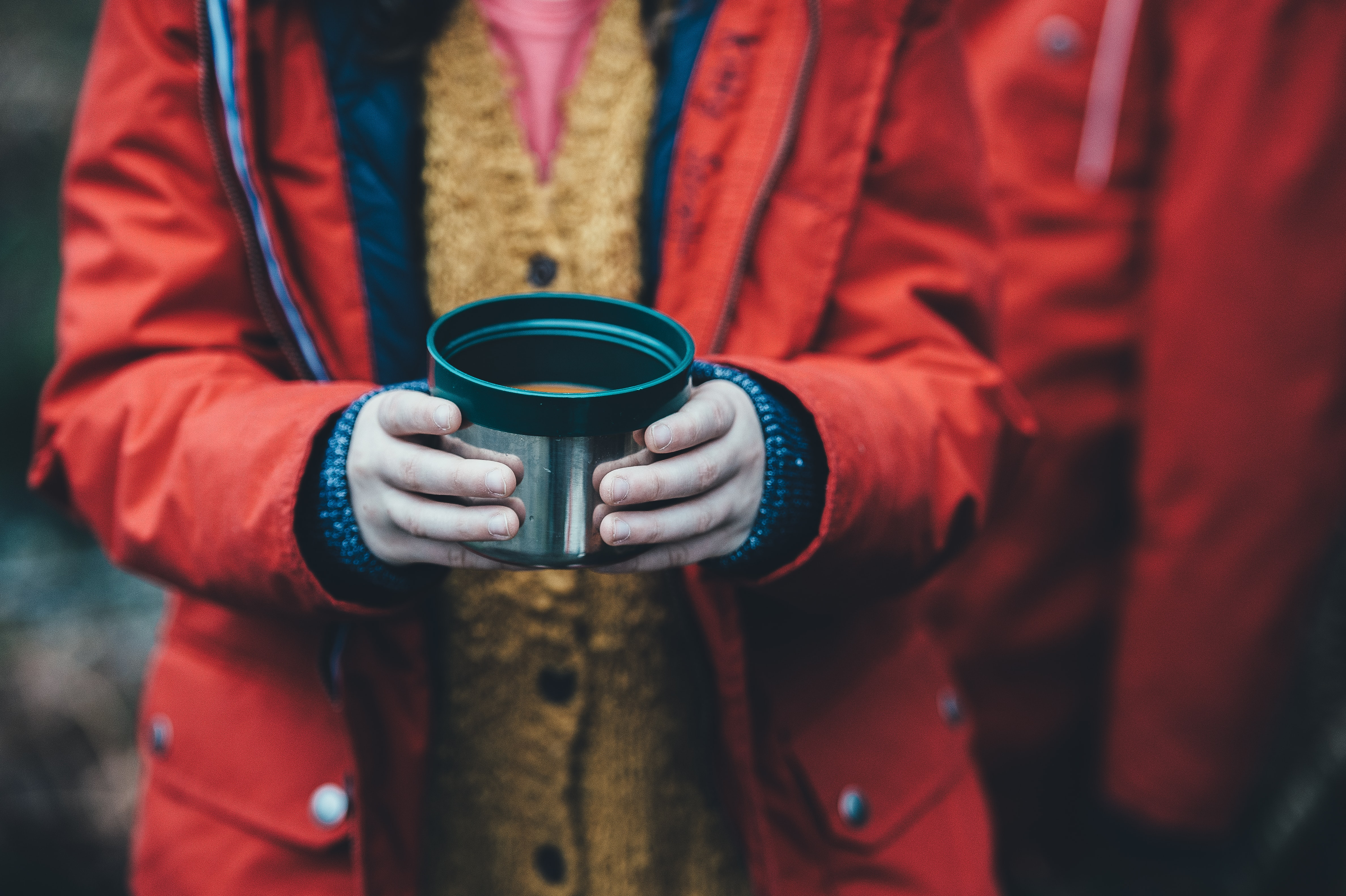 Child wearing raincoat, standing in the cold and holding cup of soup in New Forest District
