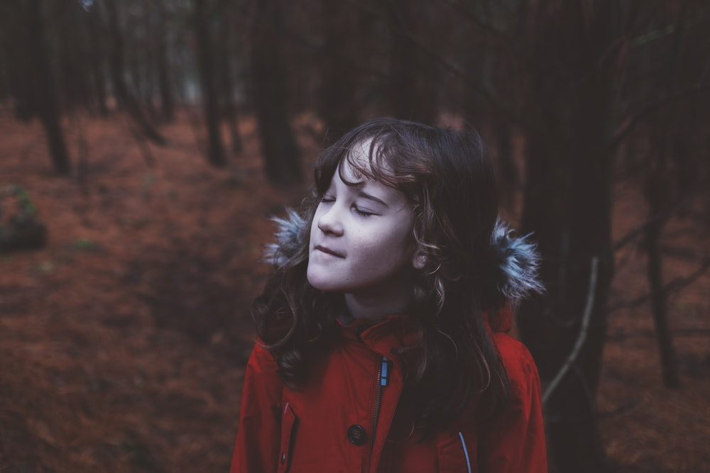 girl wearing red coat standing near trees