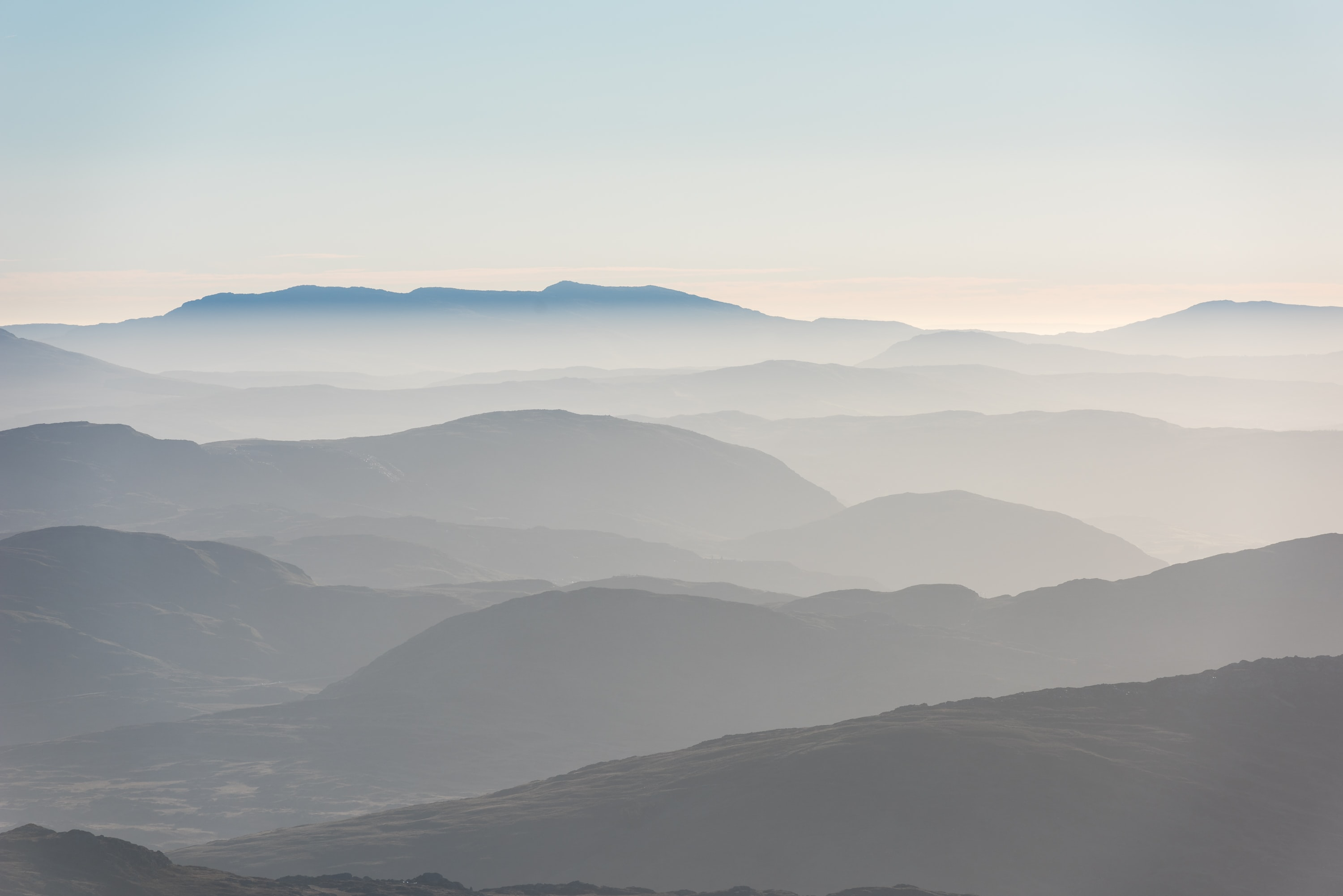 Rolling fog over hilly mountains during sunrise at Snowdonia National Park