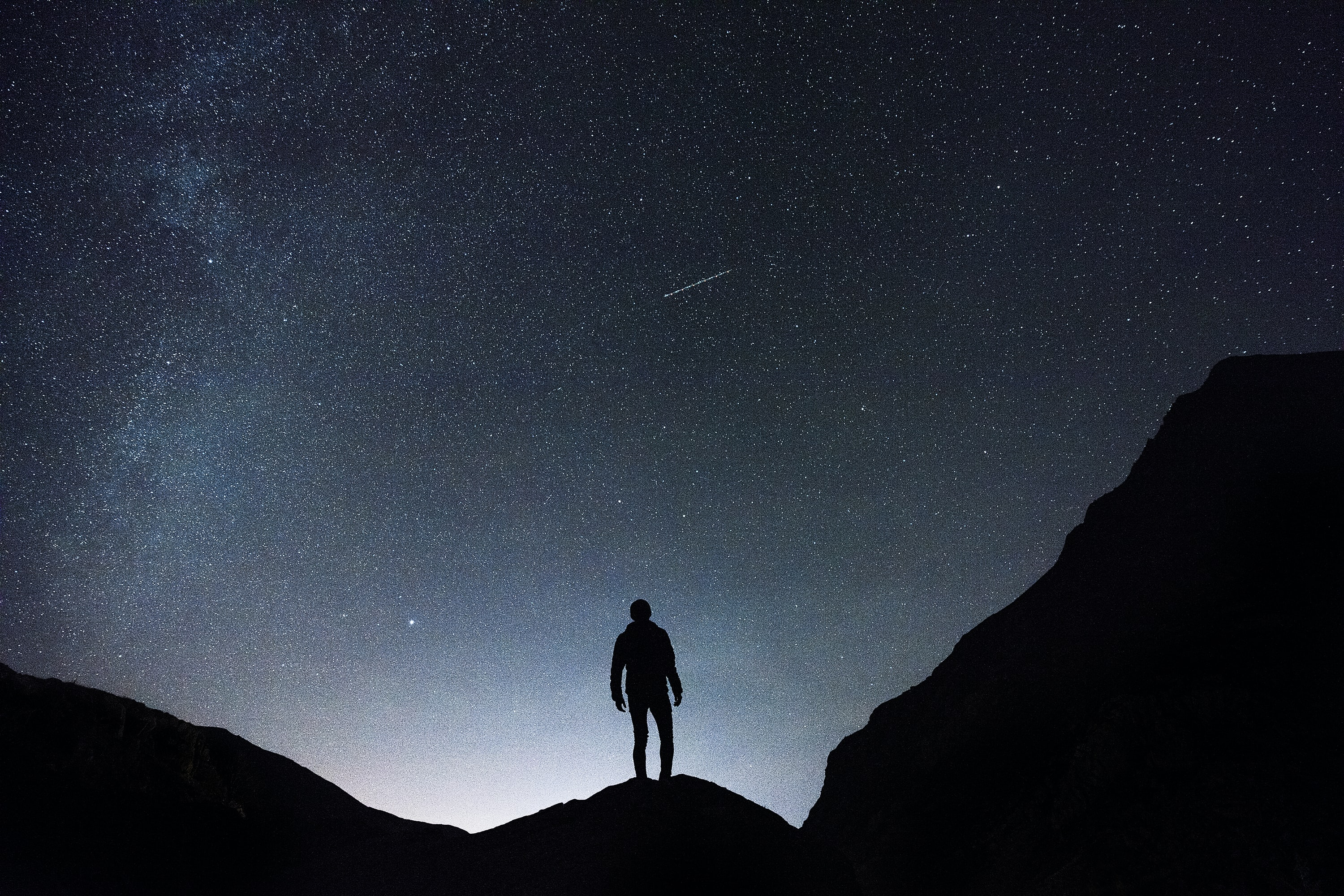 silhouette of man standing on hill during starry night