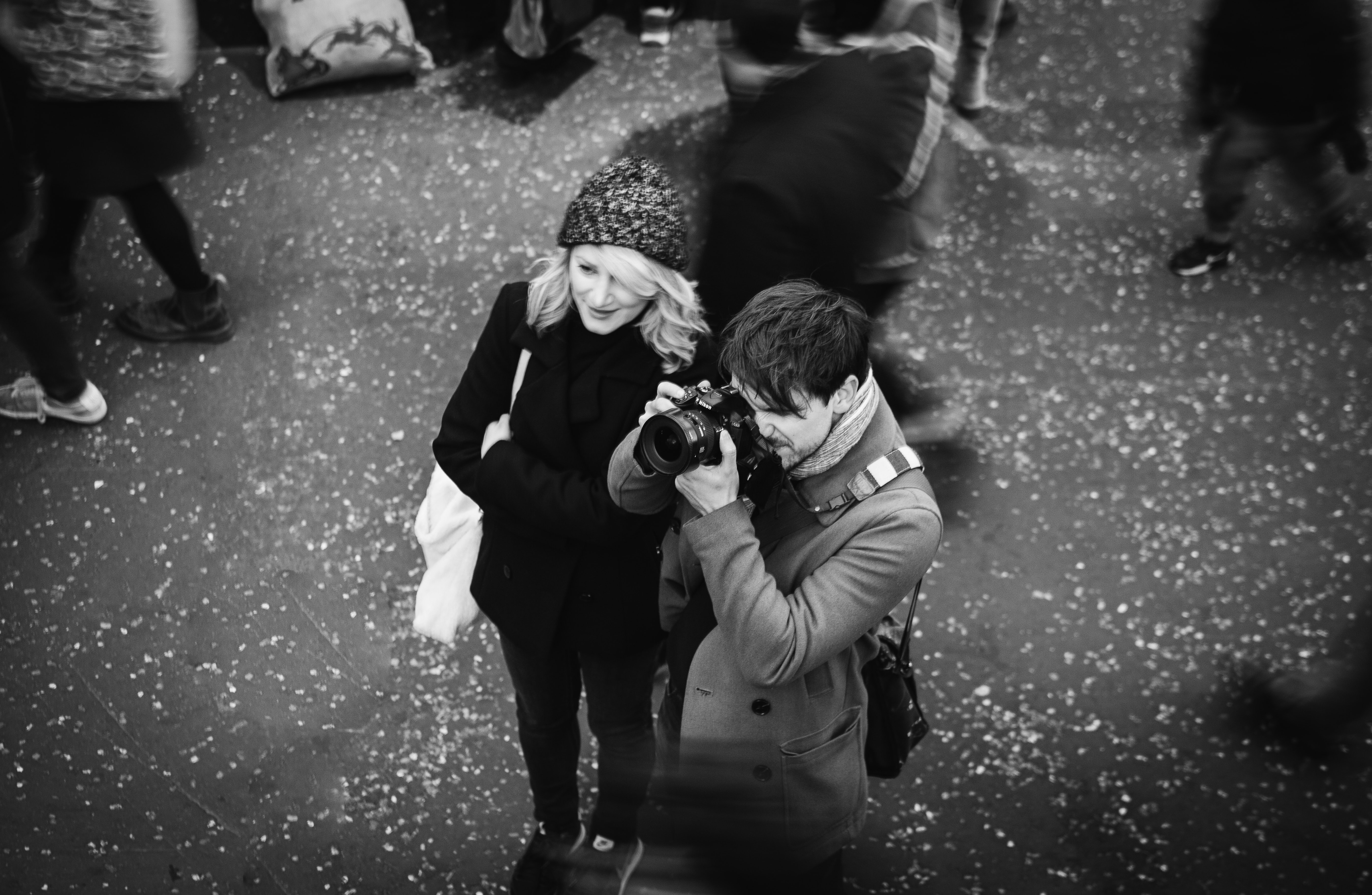 Black and white shot of woman in hat and man taking picture in South Bank
