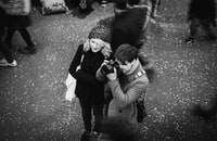 grayscale photography of man taking a photo