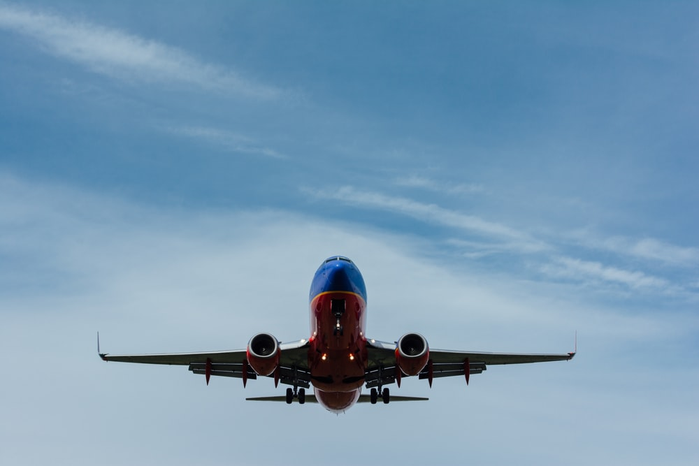 blue and red airplane on sky