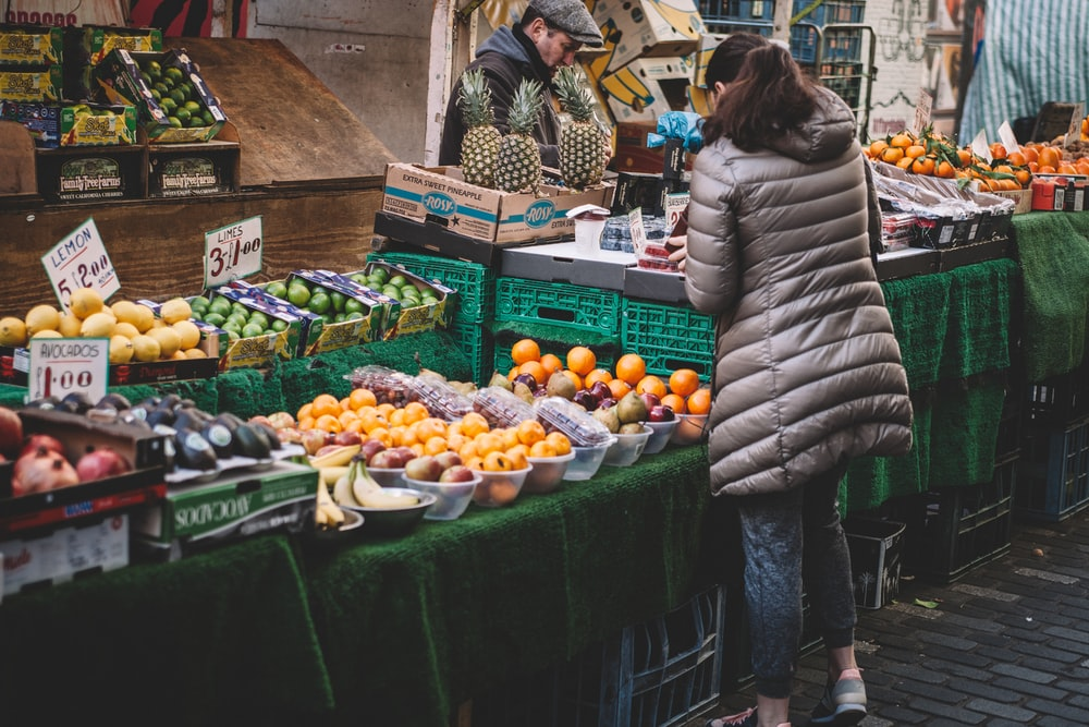 woman in front of fruit stands in market