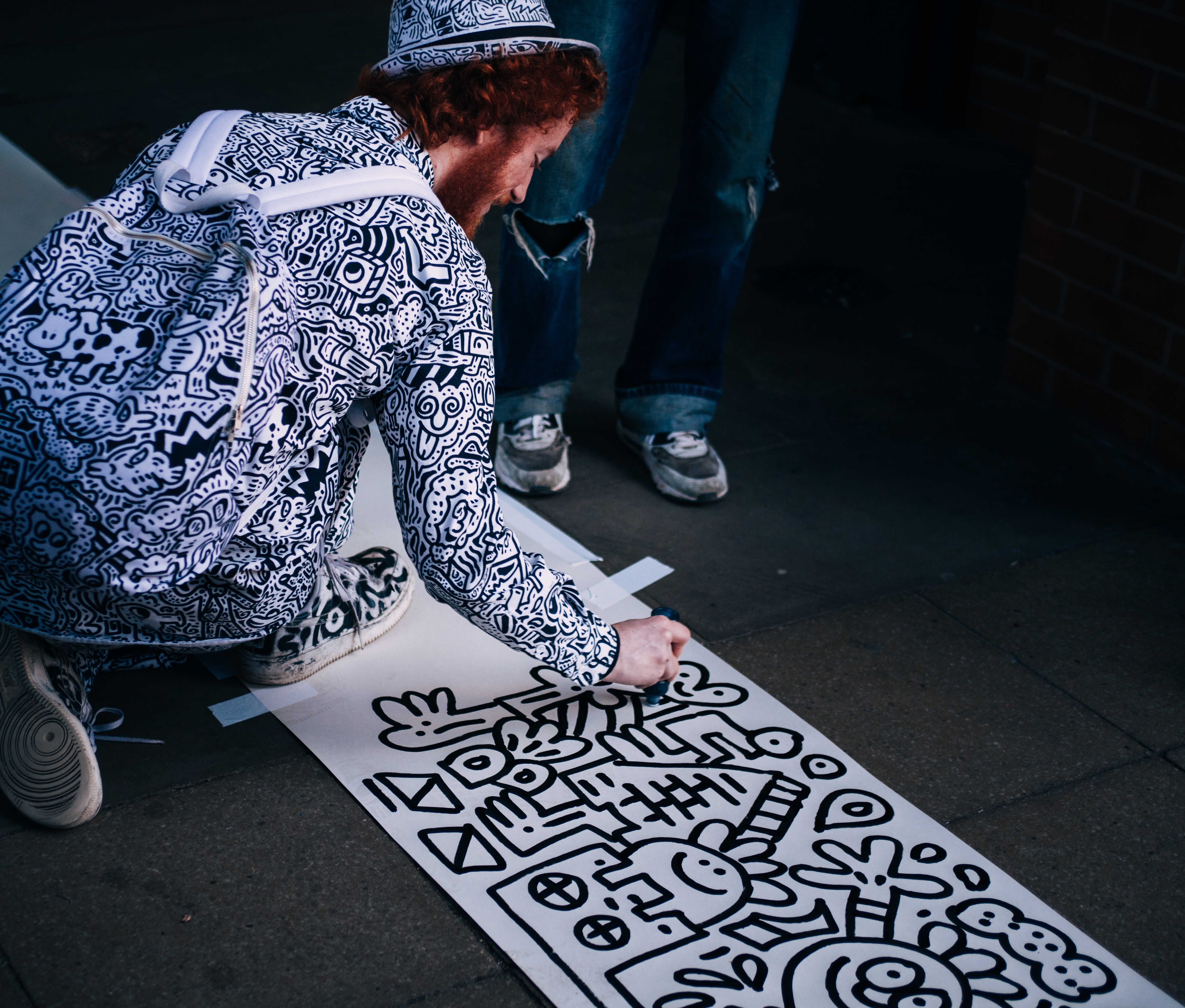 South Bank artist wearing a backpack and hat drawing art while sitting on pavement