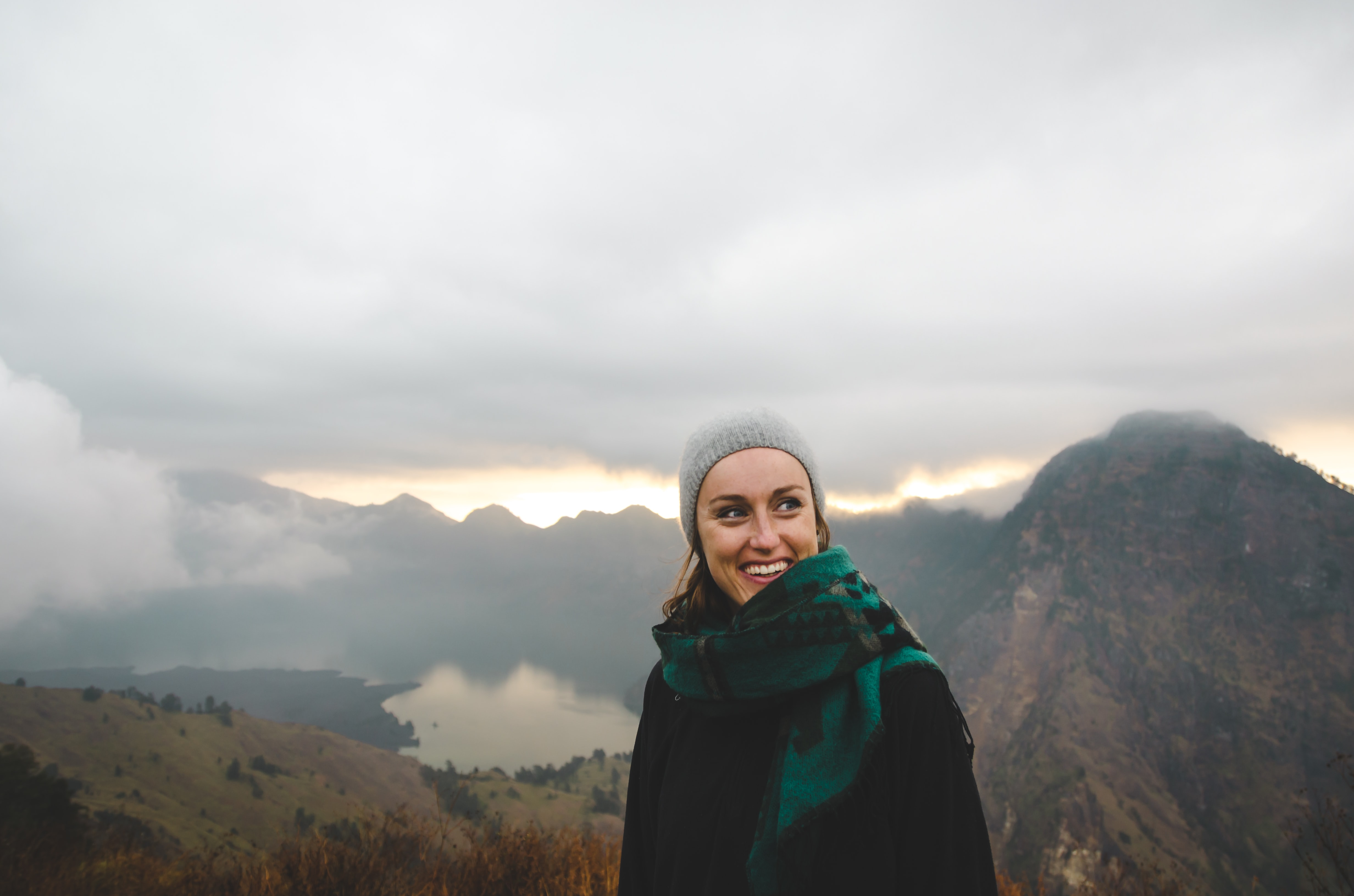 A woman wearing a scarf and a hat smiling atop a cloudy Mount Rinjani