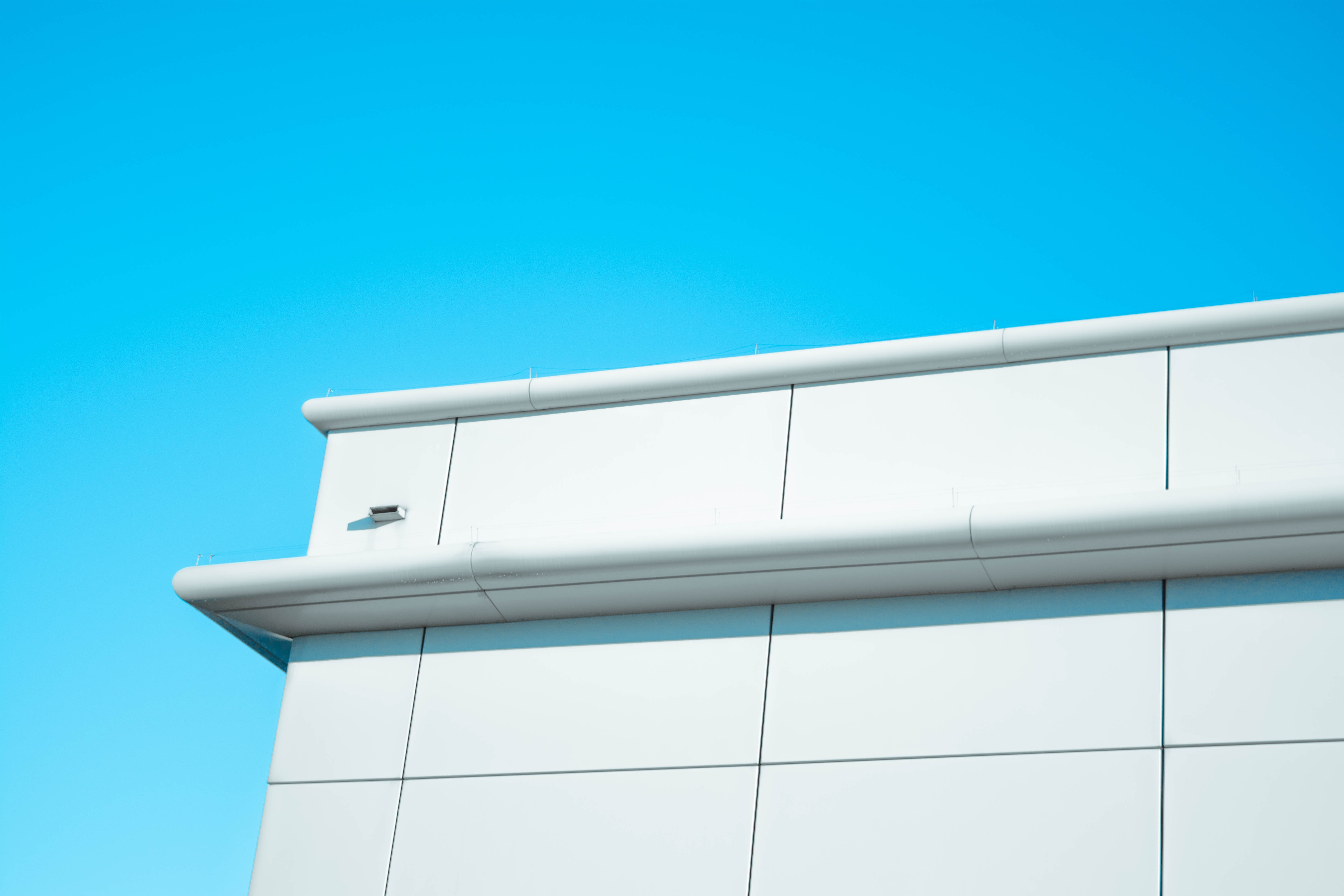 The top part of a white tiled facade with a ledge against a clear blue sky