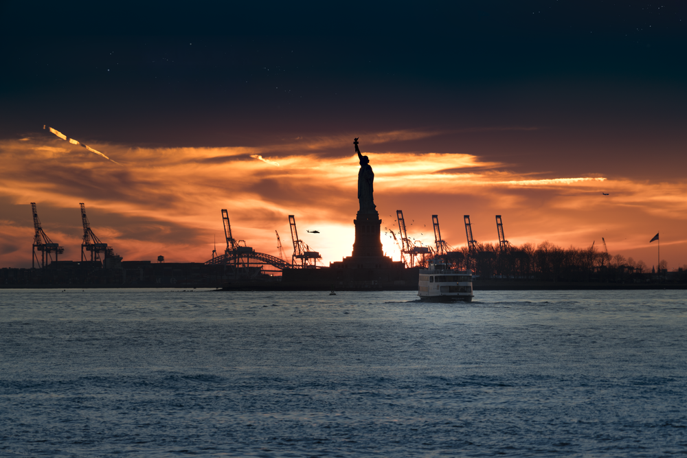silhouette of Statue of Liberty near body of water