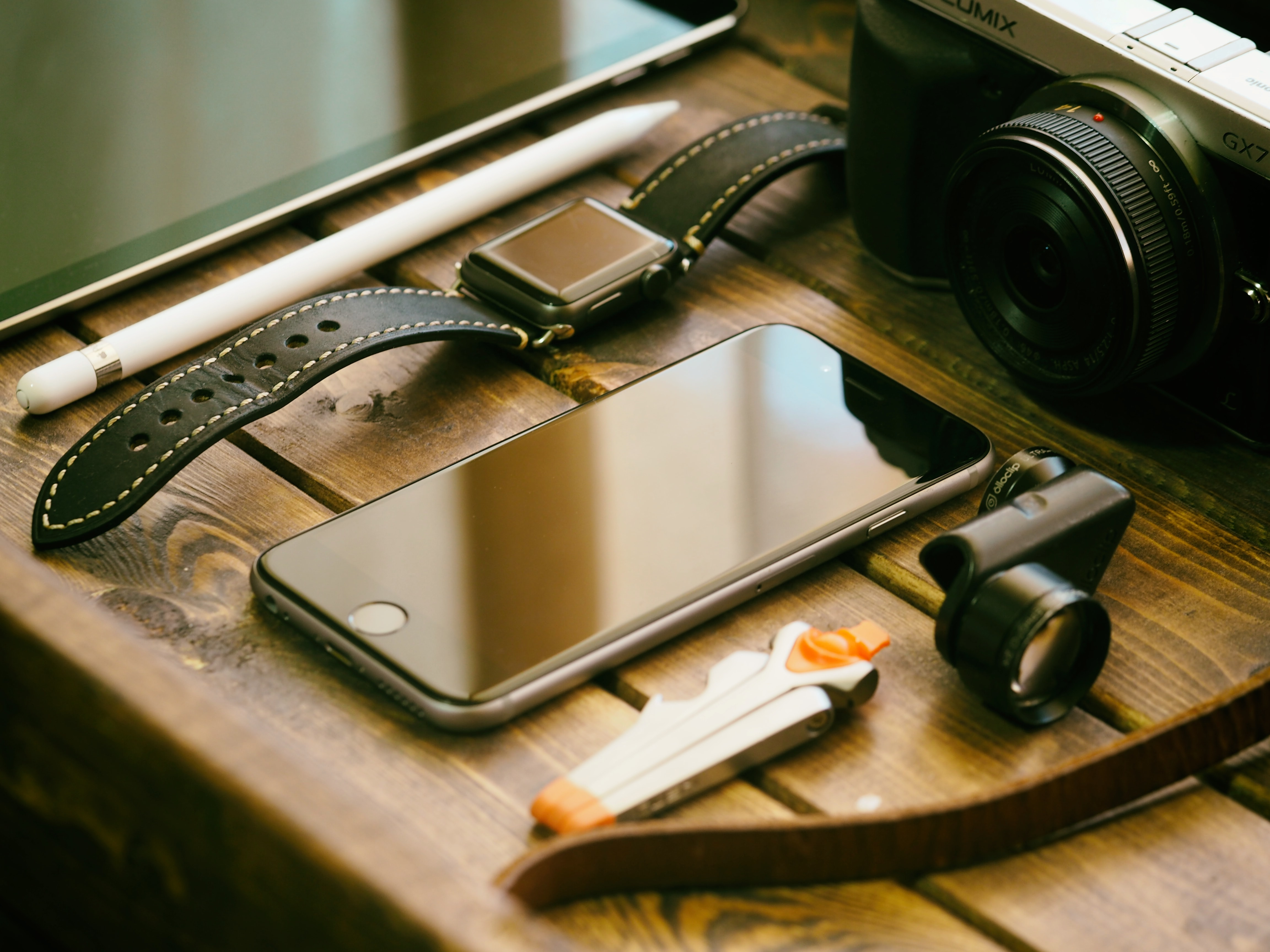 An iPhone, an Apple Watch and a digital camera on a wooden surface