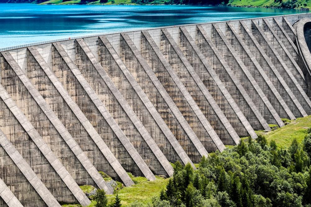gray concrete dam near green trees