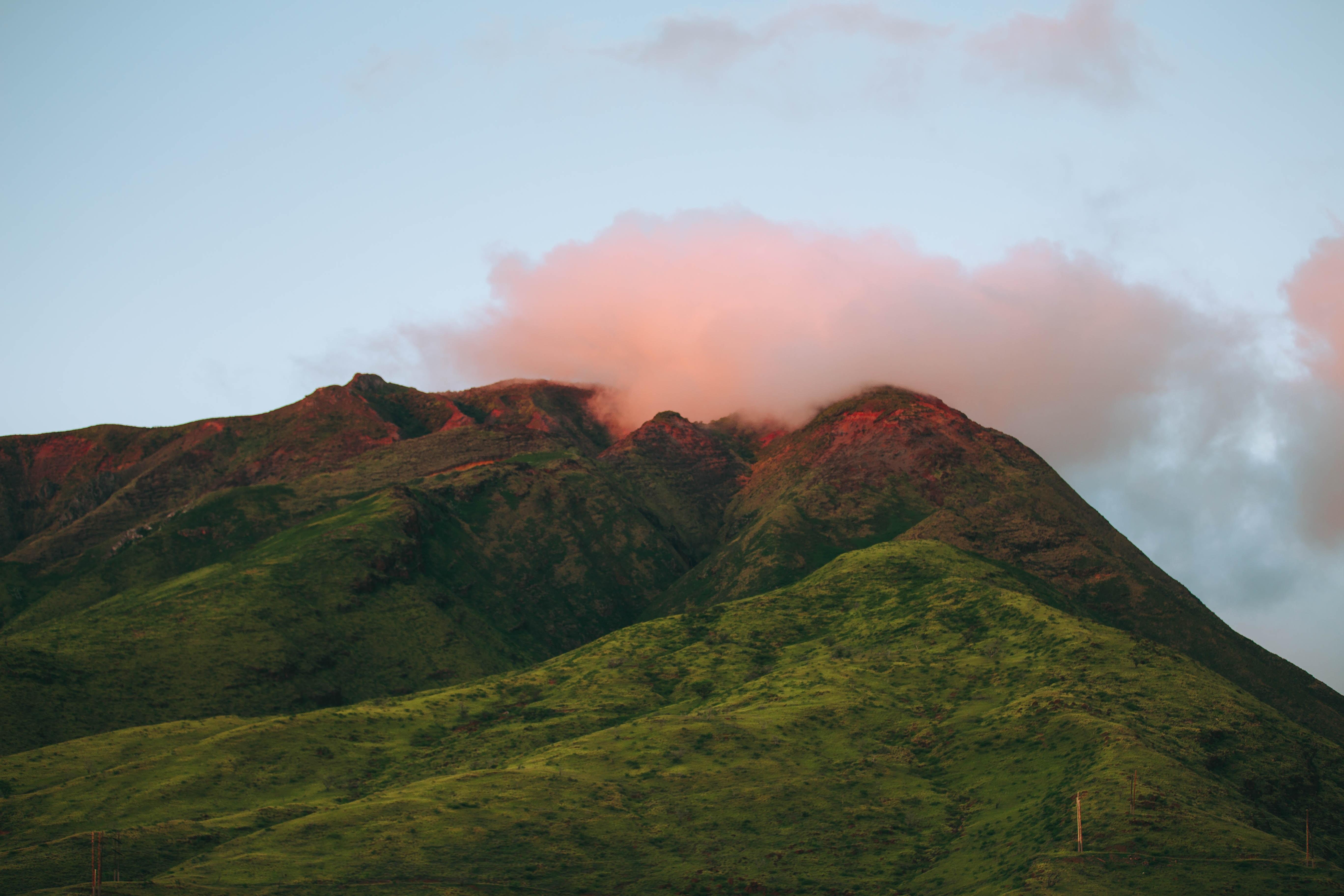 Setting sun shining through clouds on green mountaintops