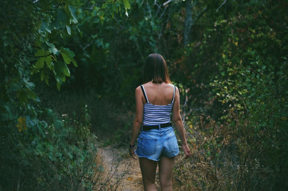 woman on pathway between trees