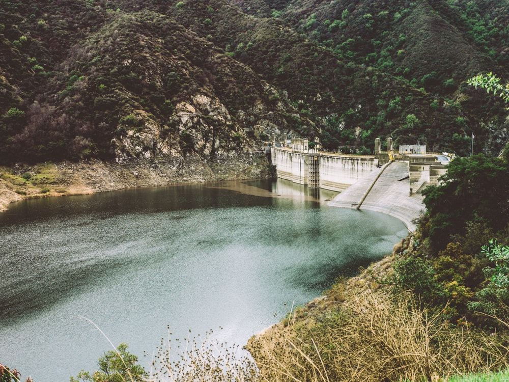 body of water in the middle of hills and concrete wall