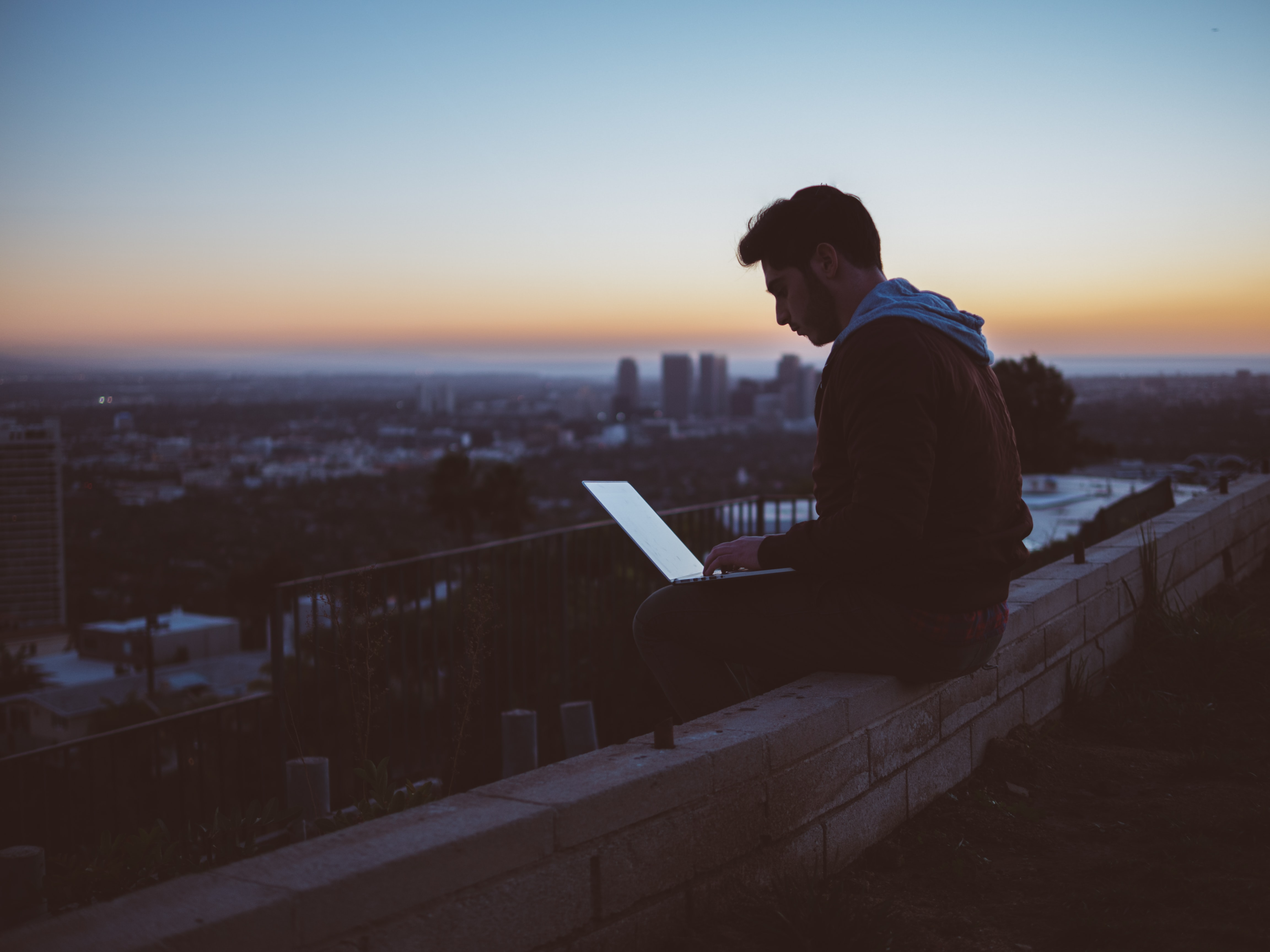 A young man working on a laptop while seated on a ledge in a city during sunset