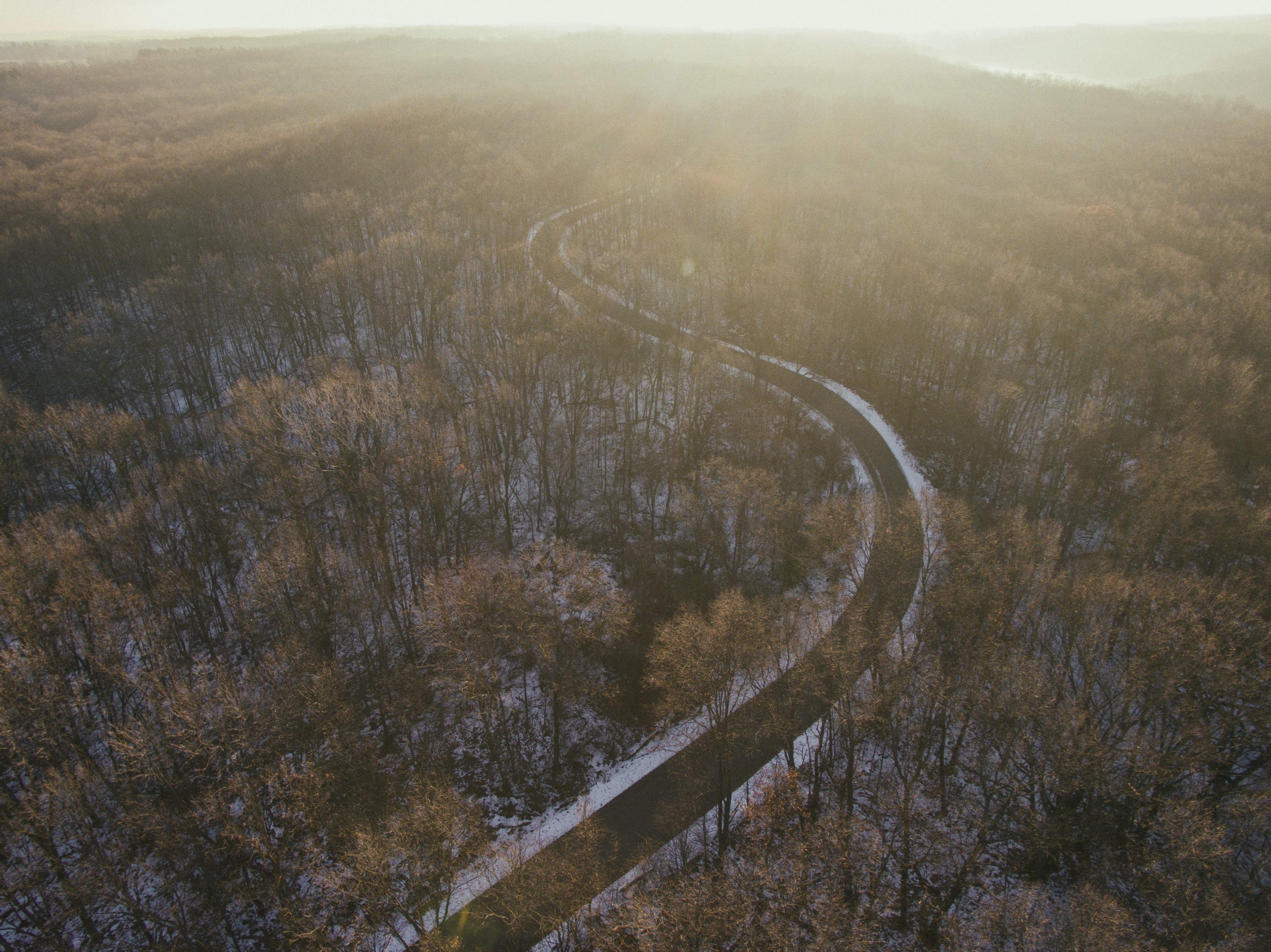 Drone shot of a winding road through a forest in Holly, Michigan on a winter's day