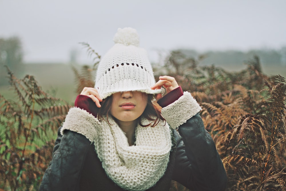 woman in white black sweater holding white knit cap
