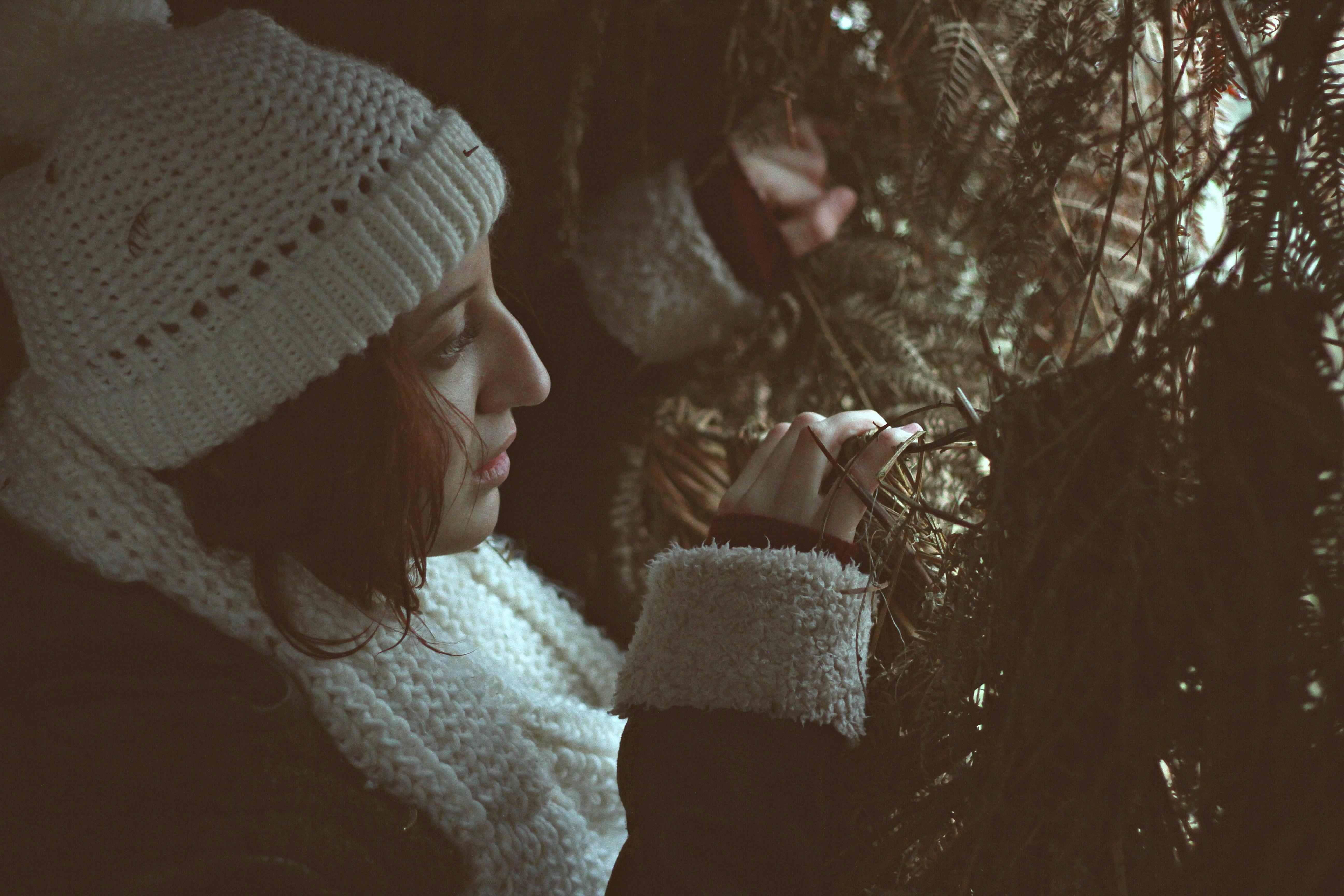 A woman in a knit cap peeking through dense needly branches