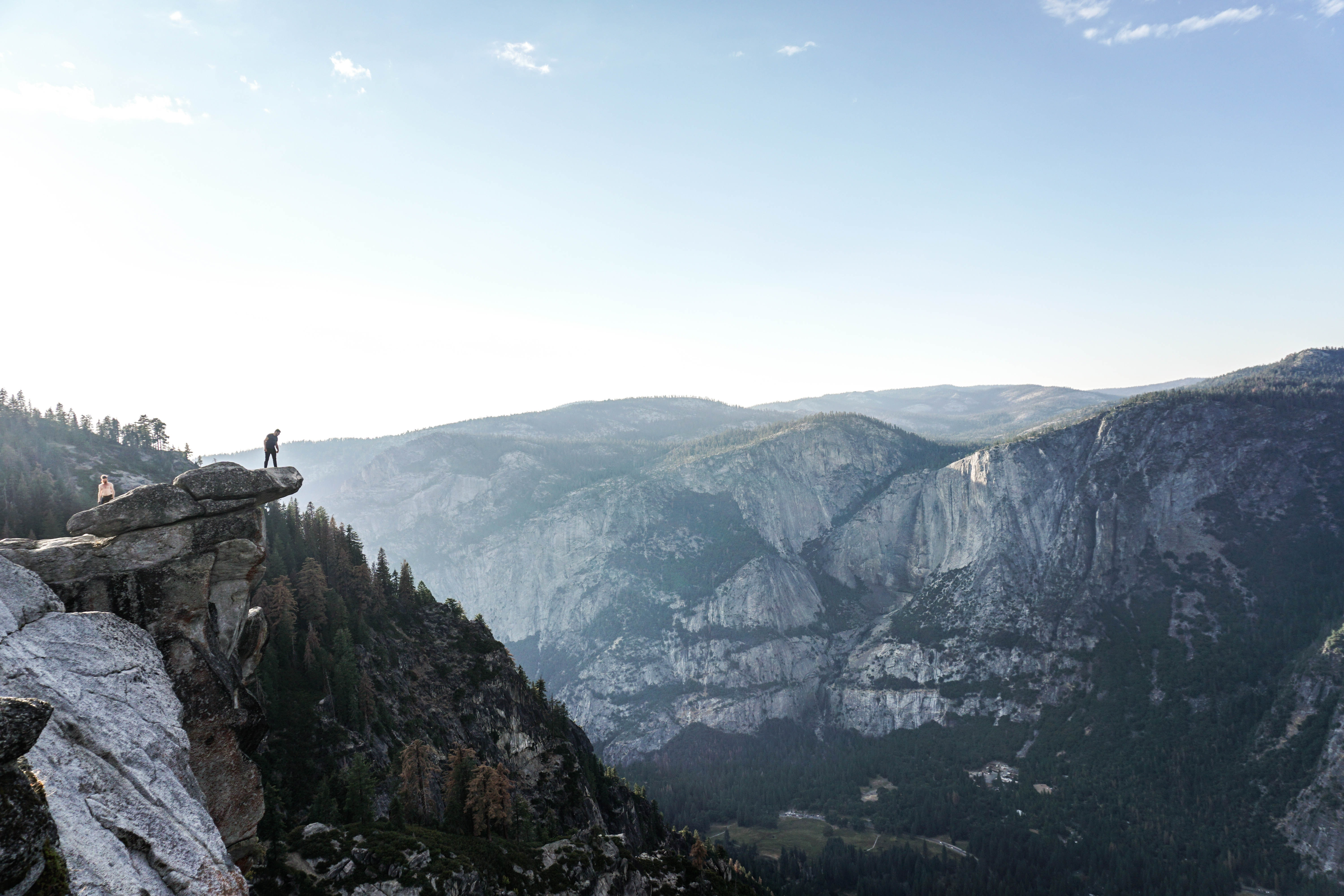 Two people on a precipice over Yosemite Valley