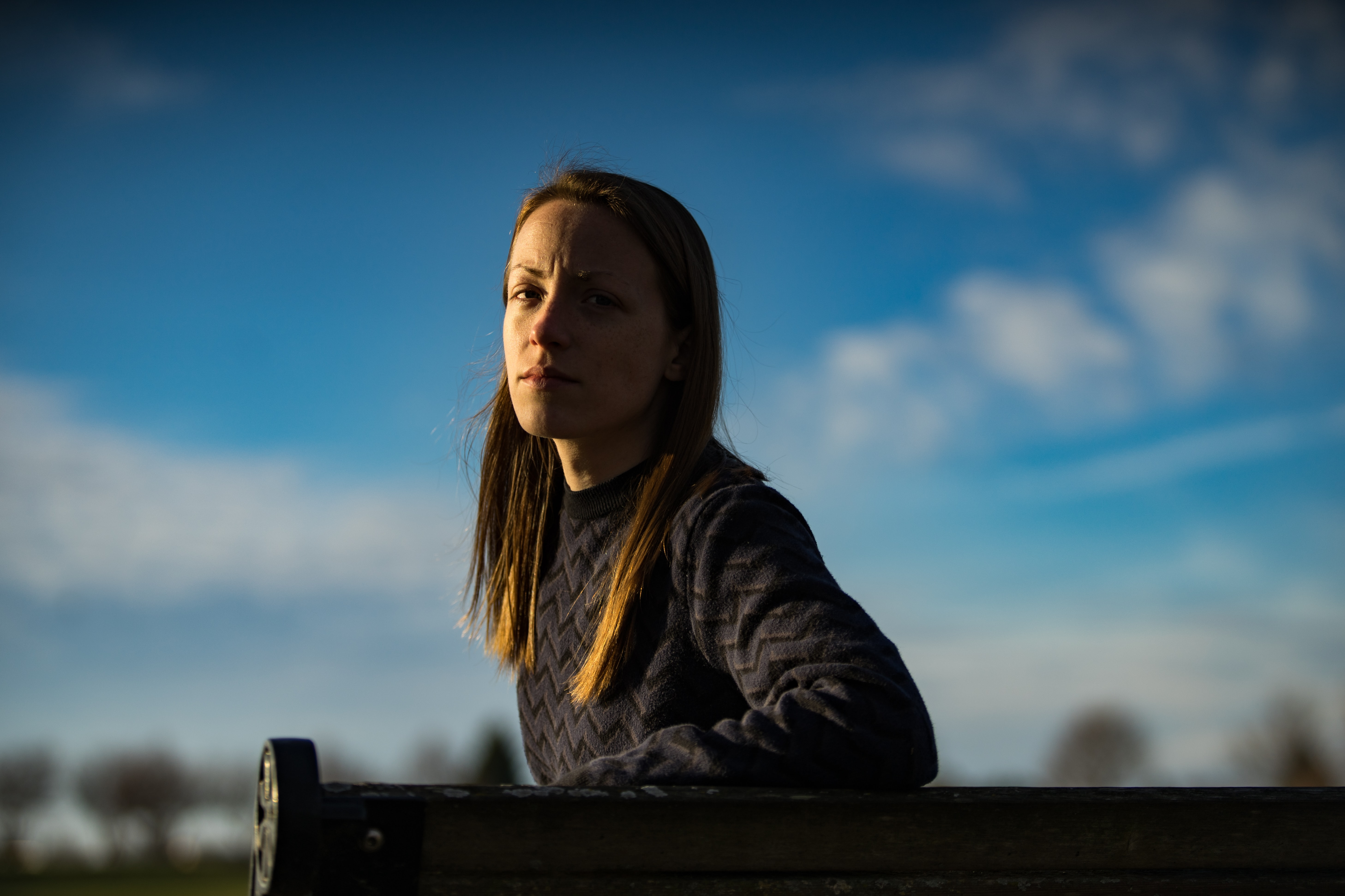 Woman sits alone on a park bench in partial shadow